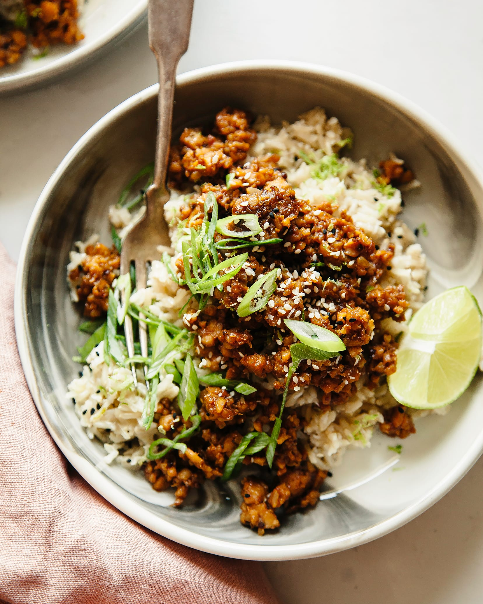 Overhead shot of a bowl of sticky ginger tempeh with coconut rice with a lime wedge alongside.