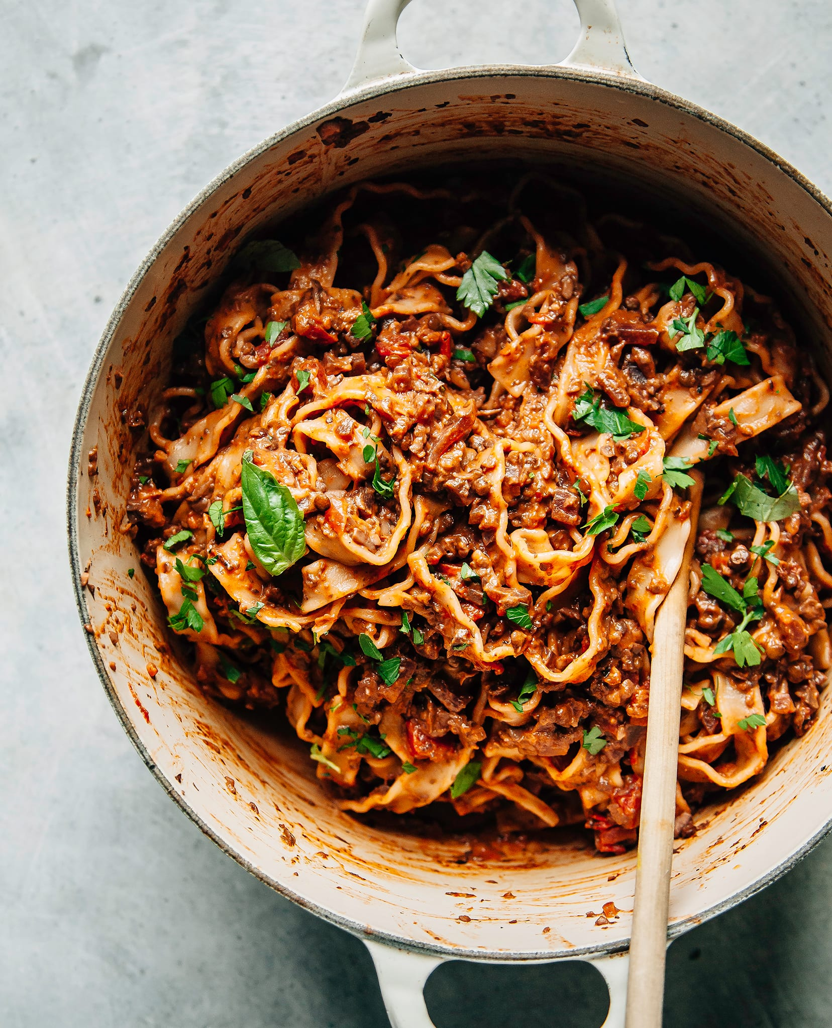 An overhead shot of a deep red, meaty vegan bolognese pasta in a pot.