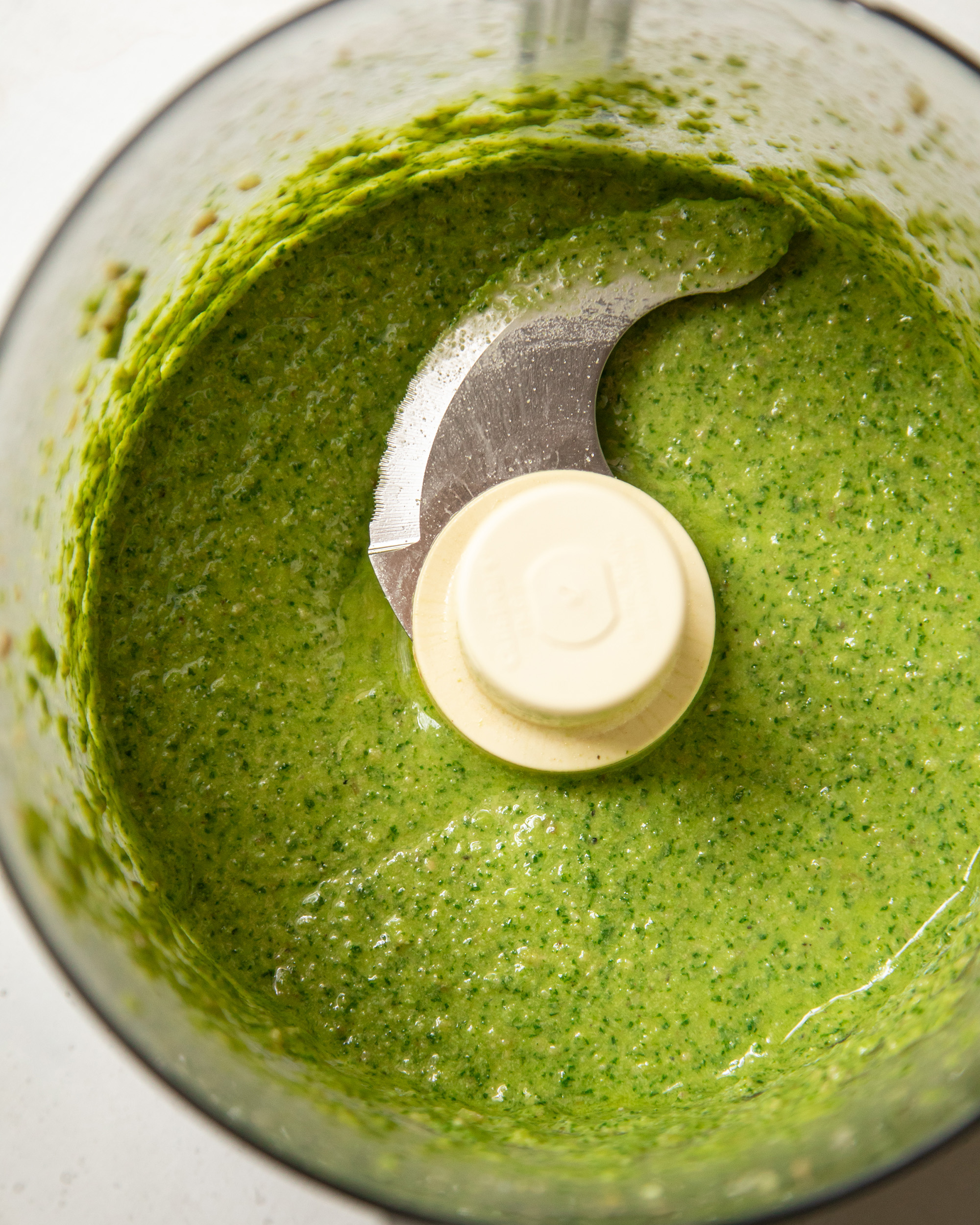 An overhead shot of a bright green pesto dressing in a food processor.