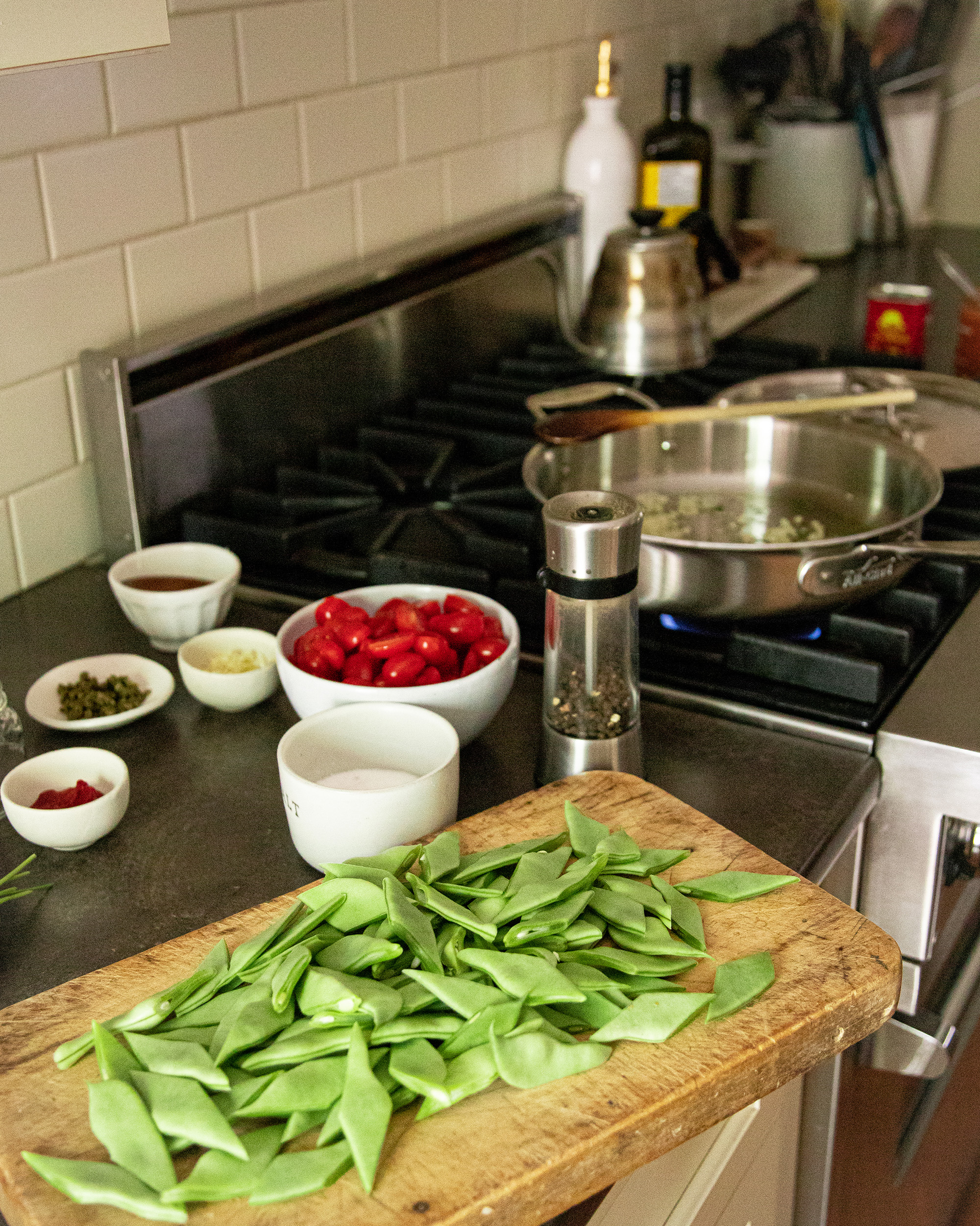 A kitchen scene featuring a gas stove and prepped ingredients on a nearby counter.