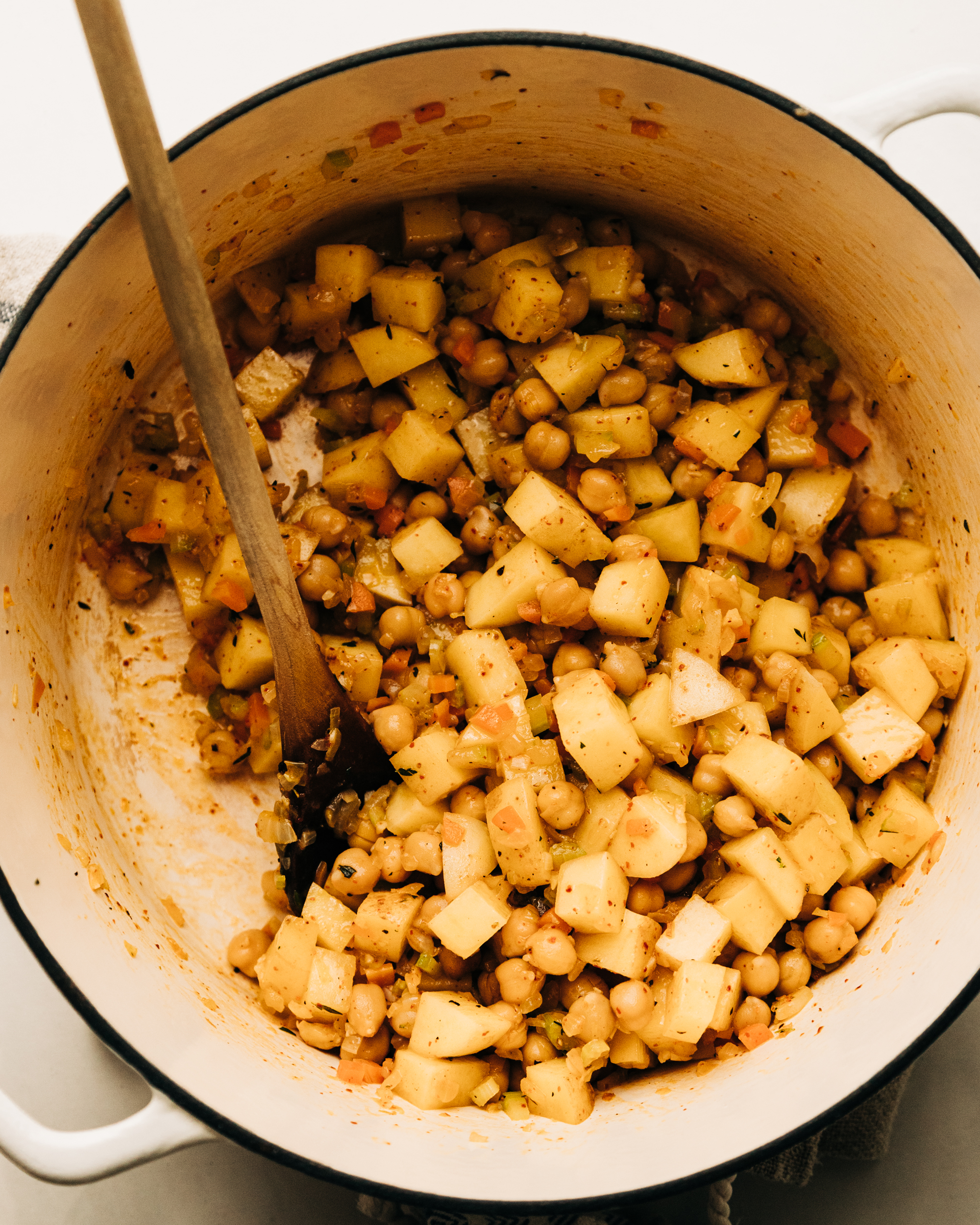 An overhead shot of sautéed chickpeas and potatoes in a white dutch oven-style pot.