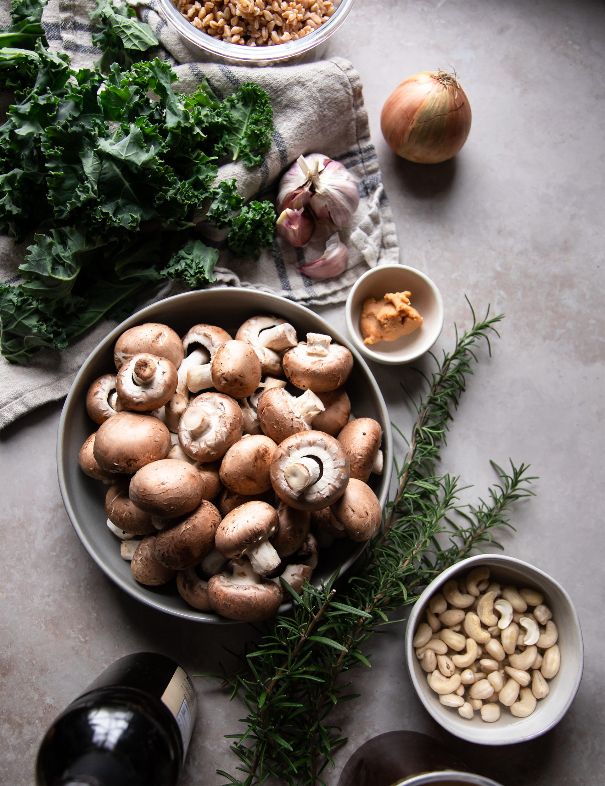 An overhead shot of ingredients on a grey stone background. There is: kale, an onion, a head of garlic, cooked farro in a bowl, a bowl of Cremini mushrooms, sprigs of rosemary, and cashews.
