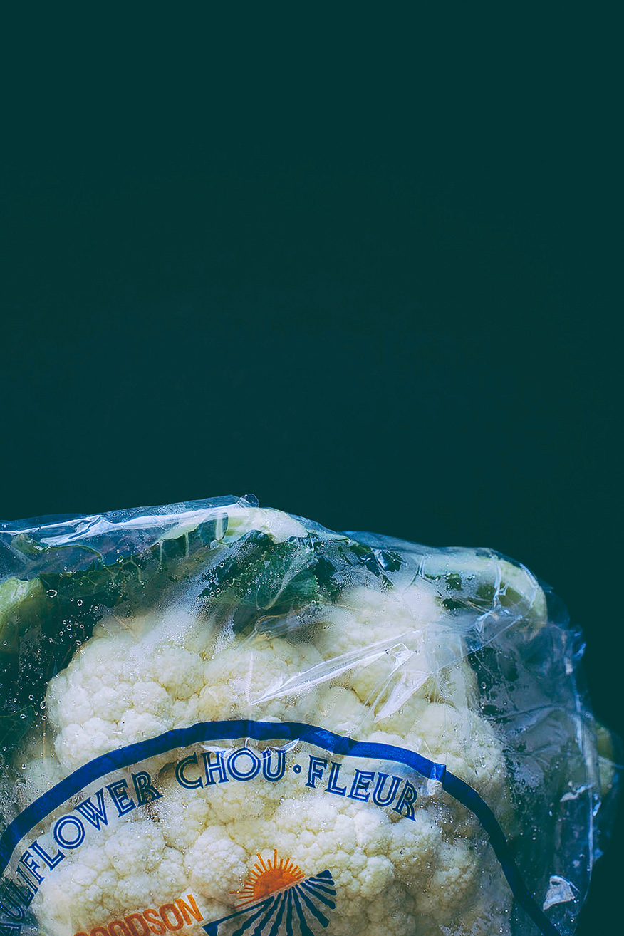 "An overhead, off-entered shot of a head of cauliflower in plastic wrap. The label says ""Chou Fleur"" in blue."