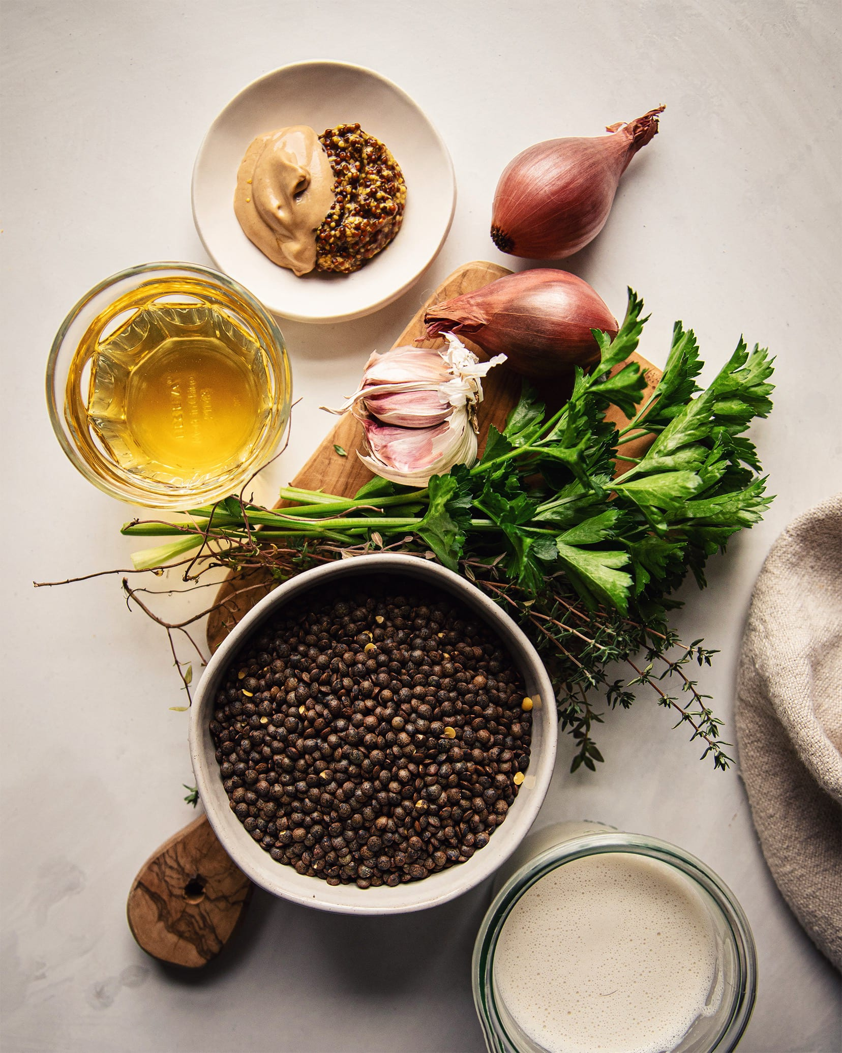 An overhead view of the ingredients used for a cooked lentil dish.  There are shallots, garlic, old-fashioned and Dijon mustard, white wine, parsley, thyme, French lentils and a cashew cream.