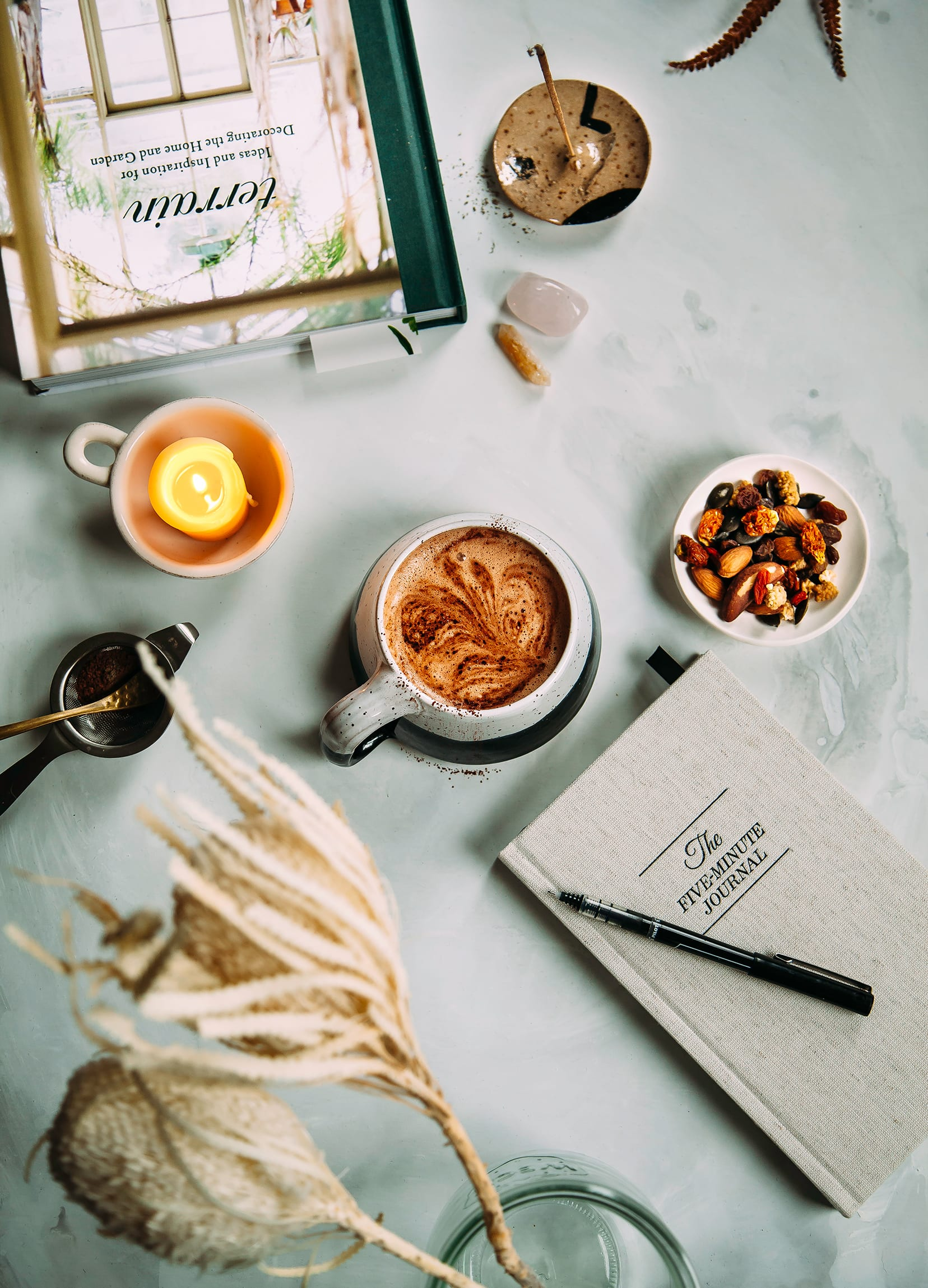 Overhead image shows a cup of hot cocoa, a lit candle, a book, a notebook, and a tray of trail mix.