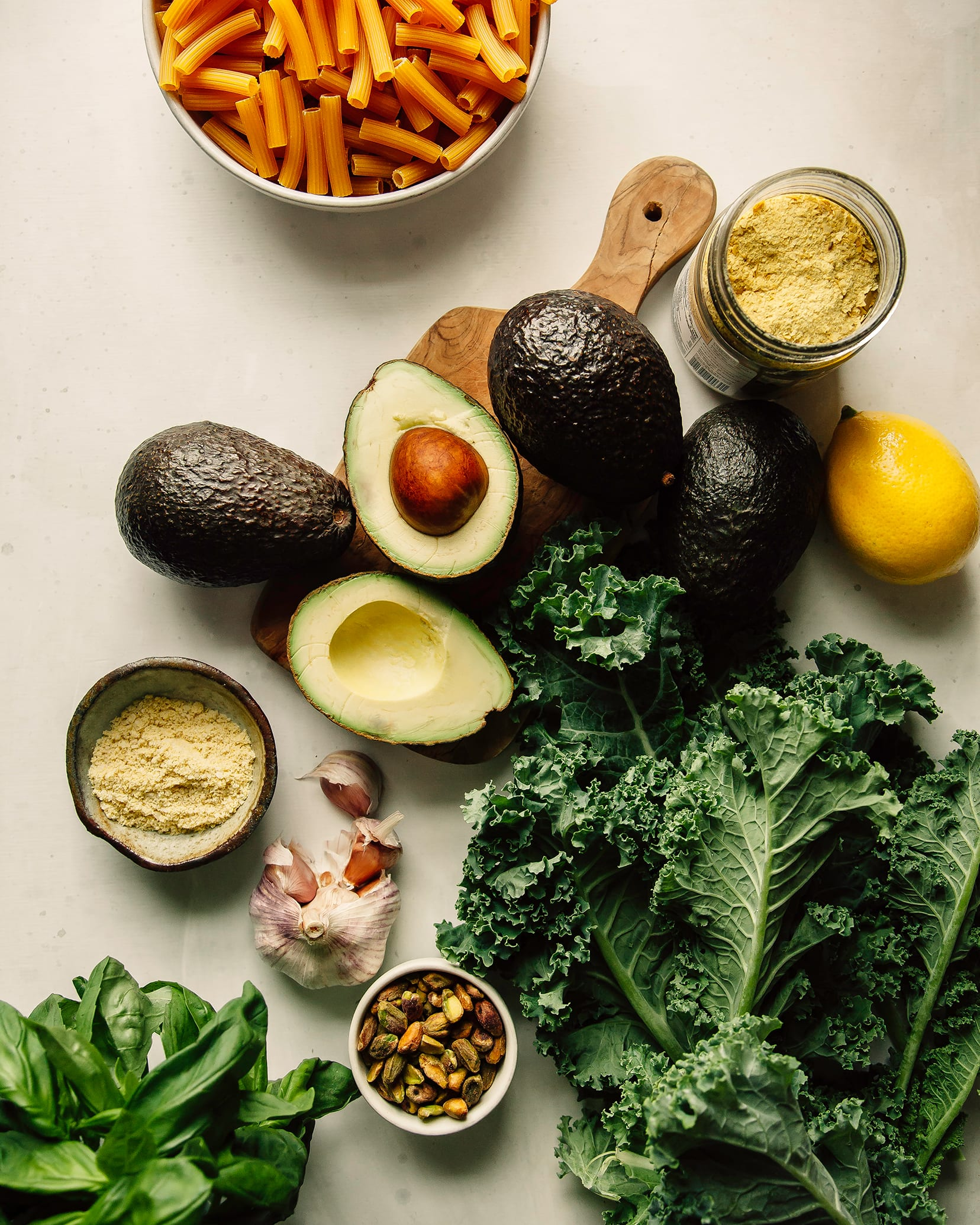 An overhead shot of ingredients for avocado pesto pasta with crispy kale on a white background.
