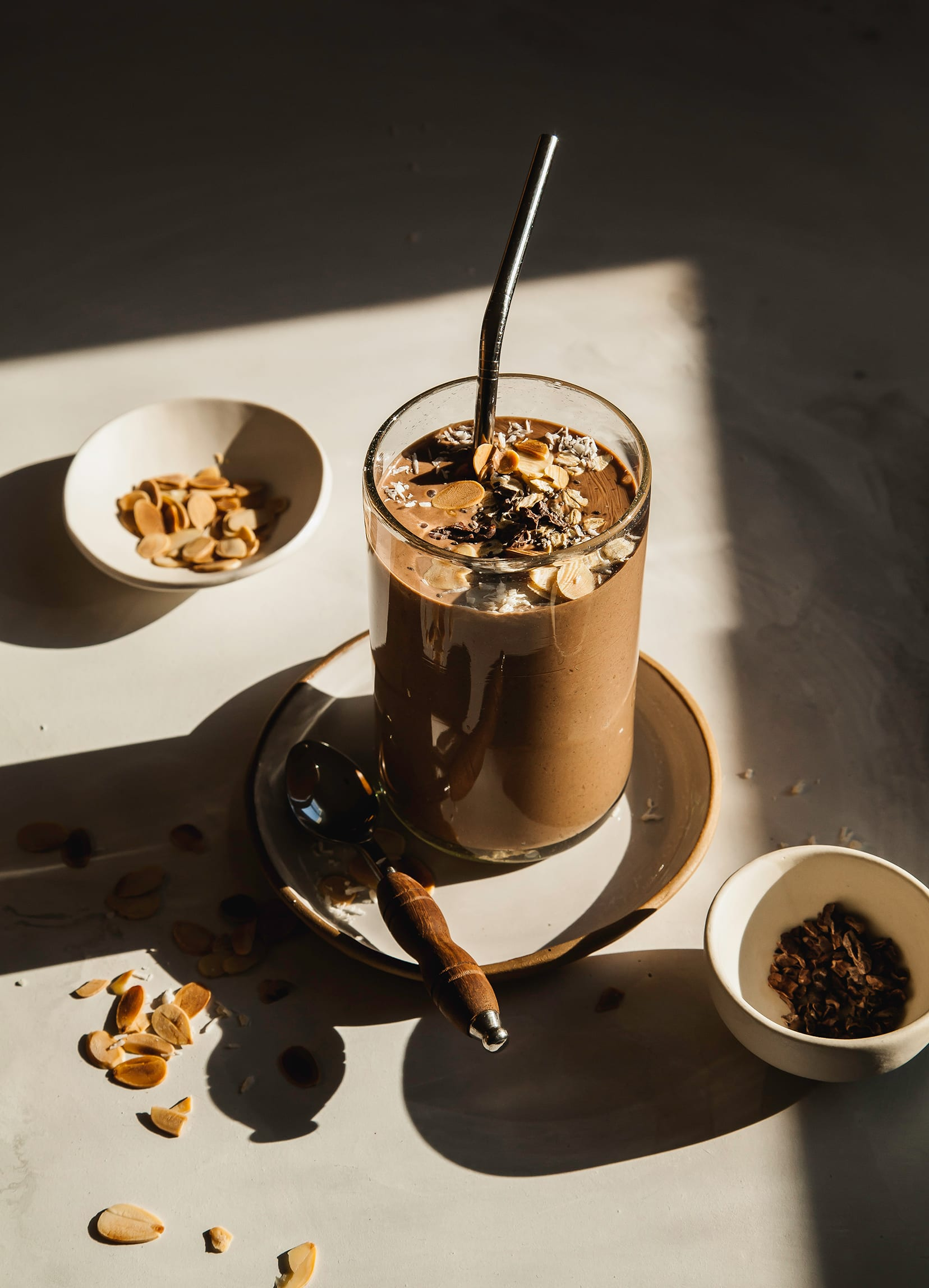 A 3/4 angle shot of a chocolate smoothie that is garnished with toasted almonds and cacao nibs. It is photographed in harsh sunlight on a mottled white background.