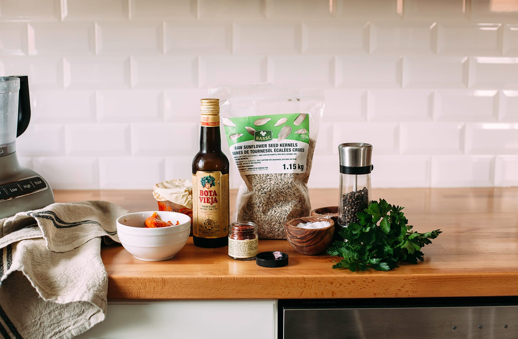 Image shows sunflower romesco sauce ingredients on a wood countertop.