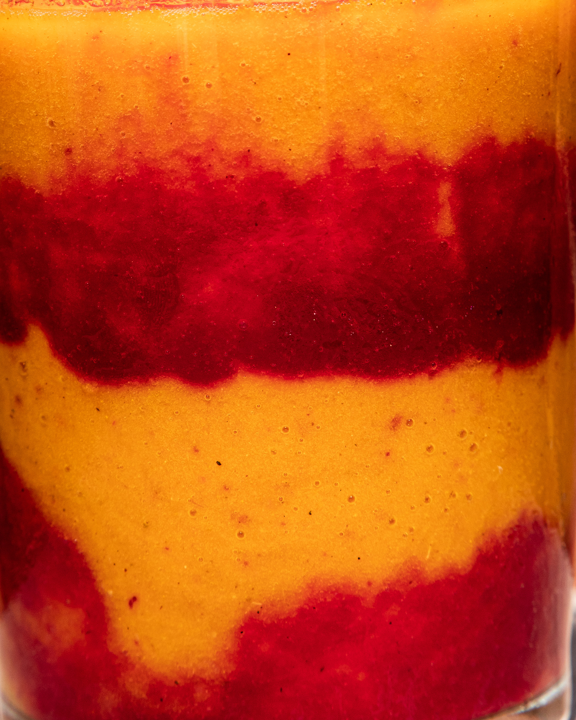 An extremely up close shot of orange and magenta smoothie layers in a clear glass.