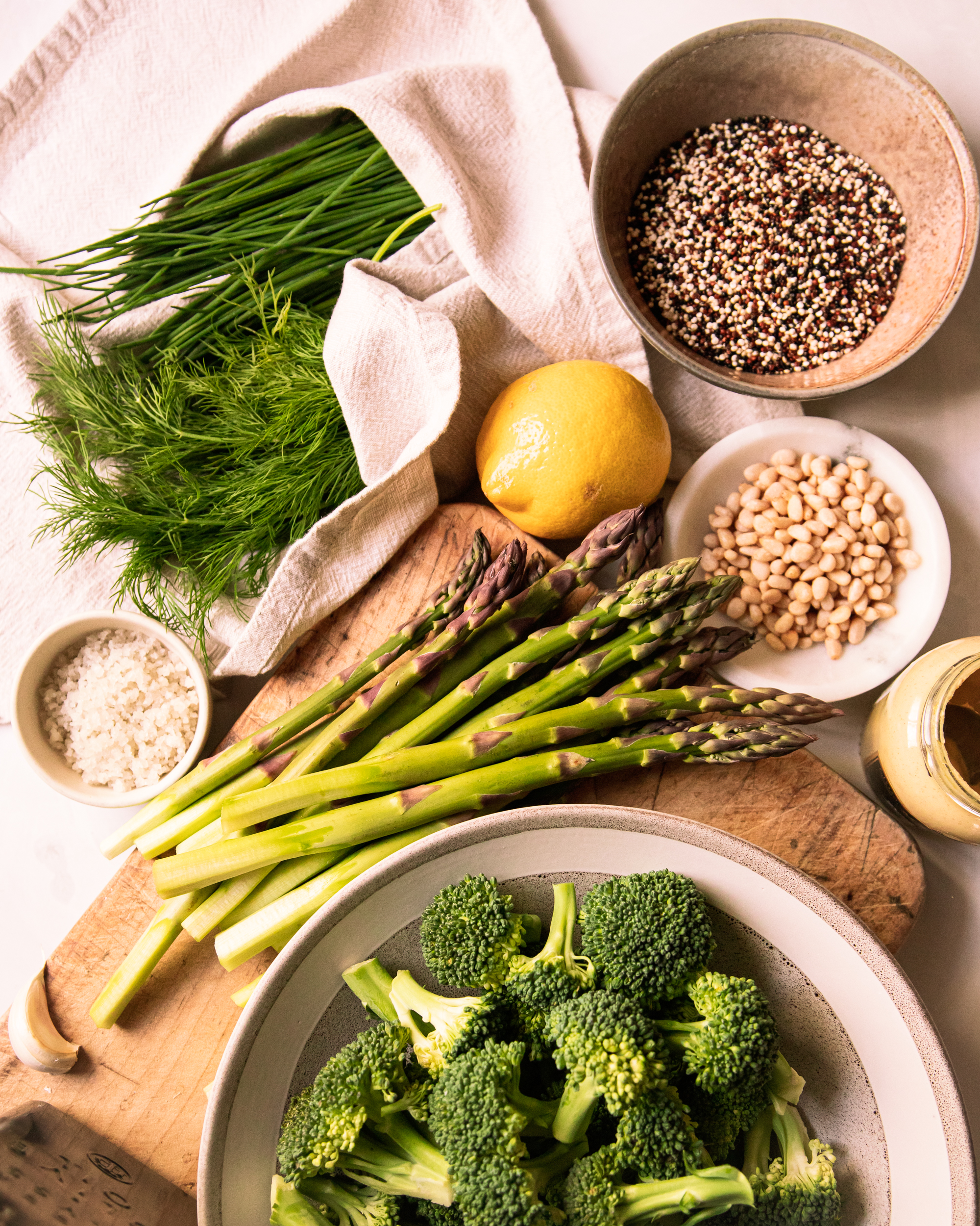 Overhead image shows ingredients for a green love quinoa salad on a worn wood and mottled white background.