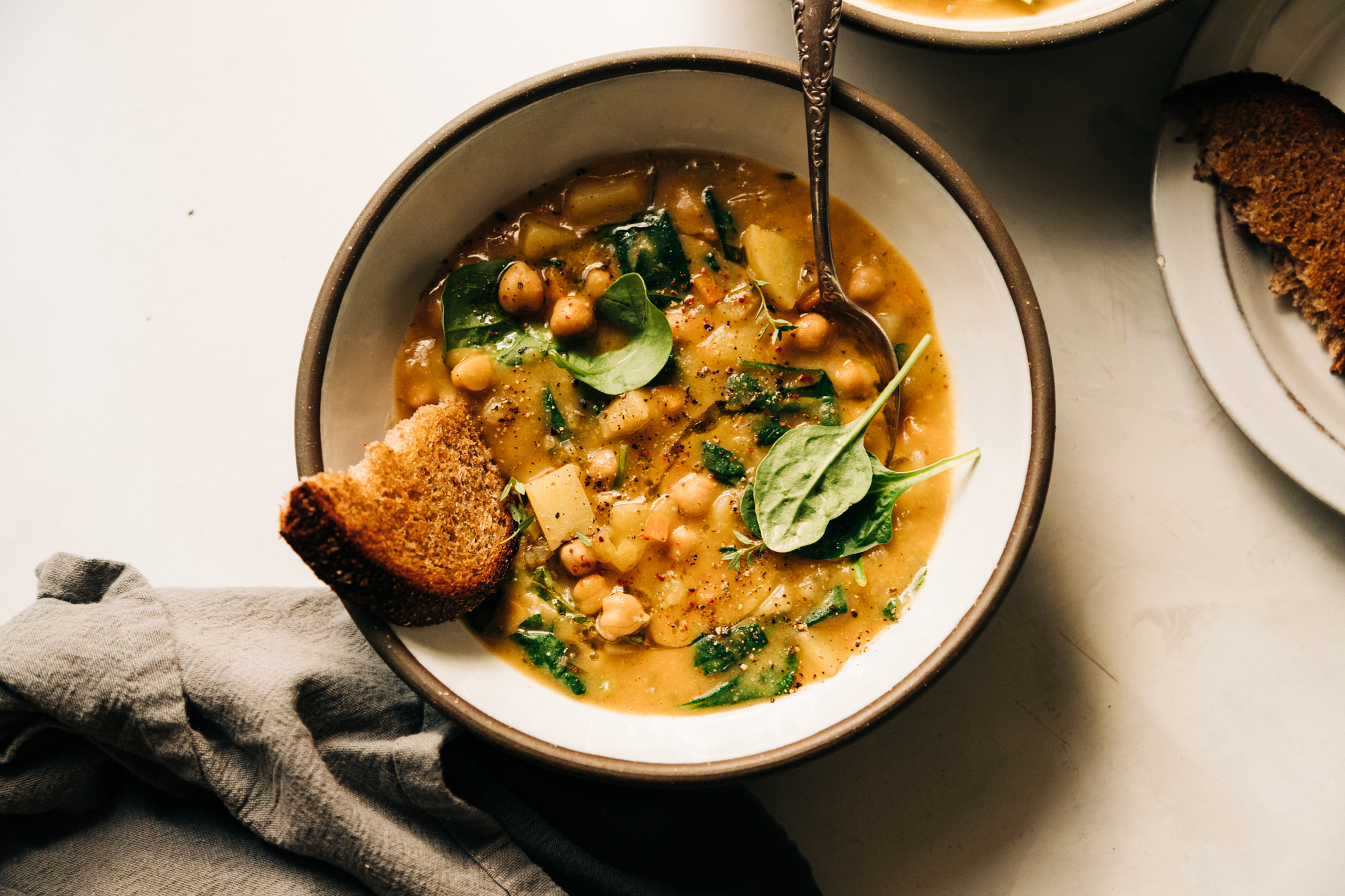 An overhead shot of a creamy and thick lemony chickpea soup with spinach and potatoes in a white ceramic bowl edges with grey. A piece of whole grain bread is sticking out of the soup.