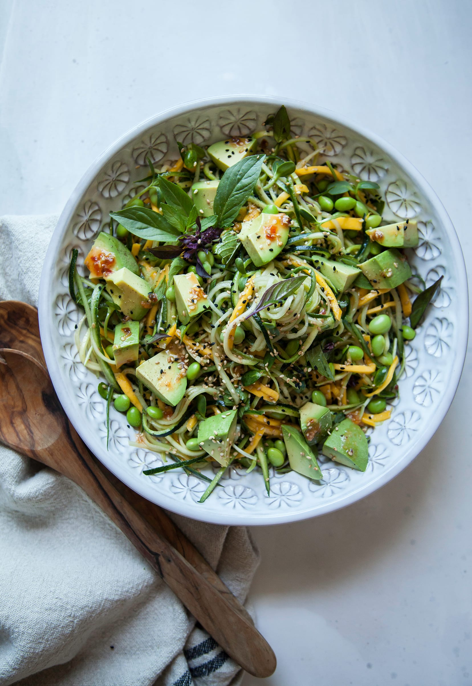 Image shows a green, veggie noodle salad with chunks of ripe avocado, mango noodles, and sesame seeds.