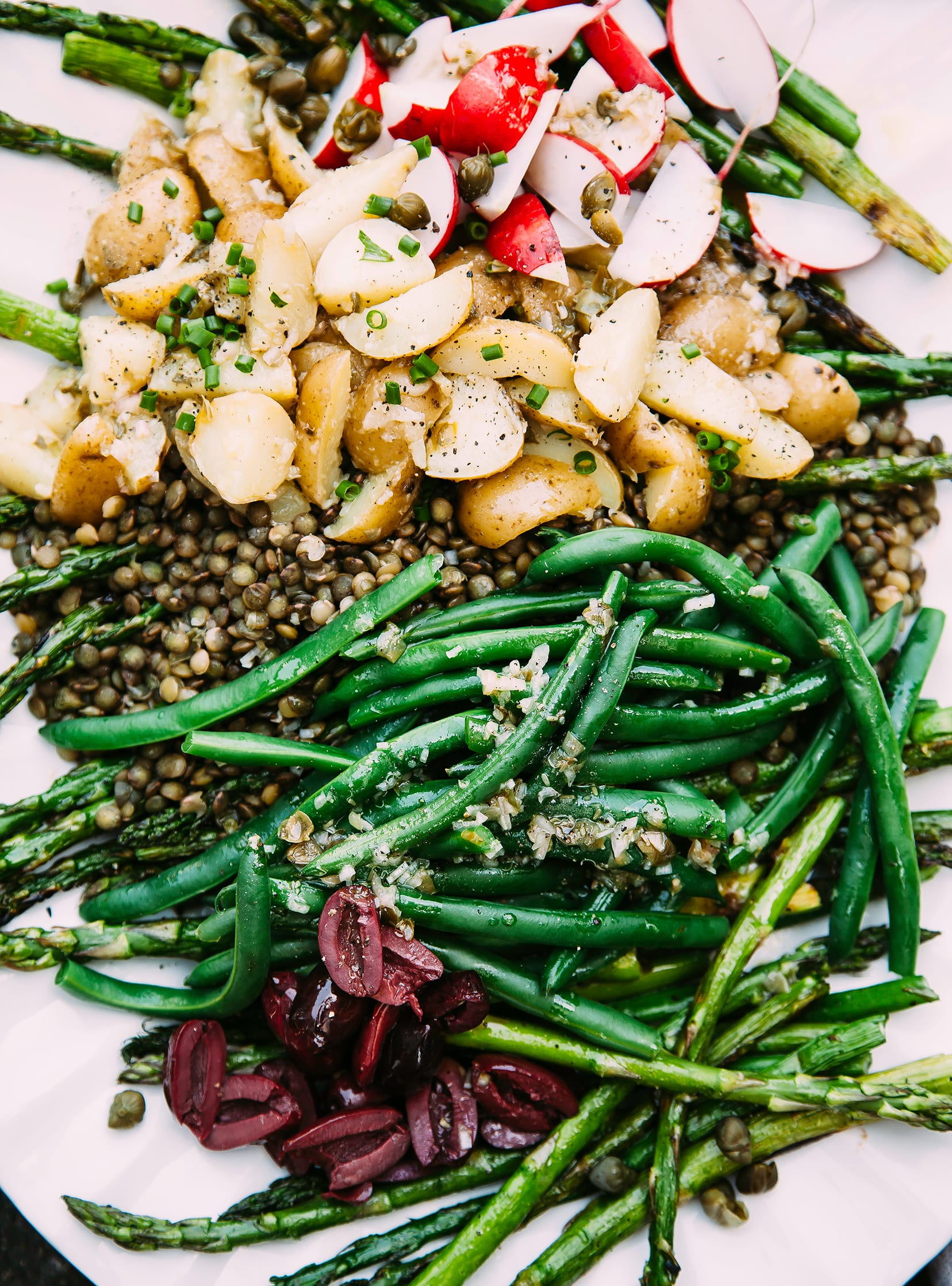 An overhead image of a vegan niçoise style salad on a white platter.