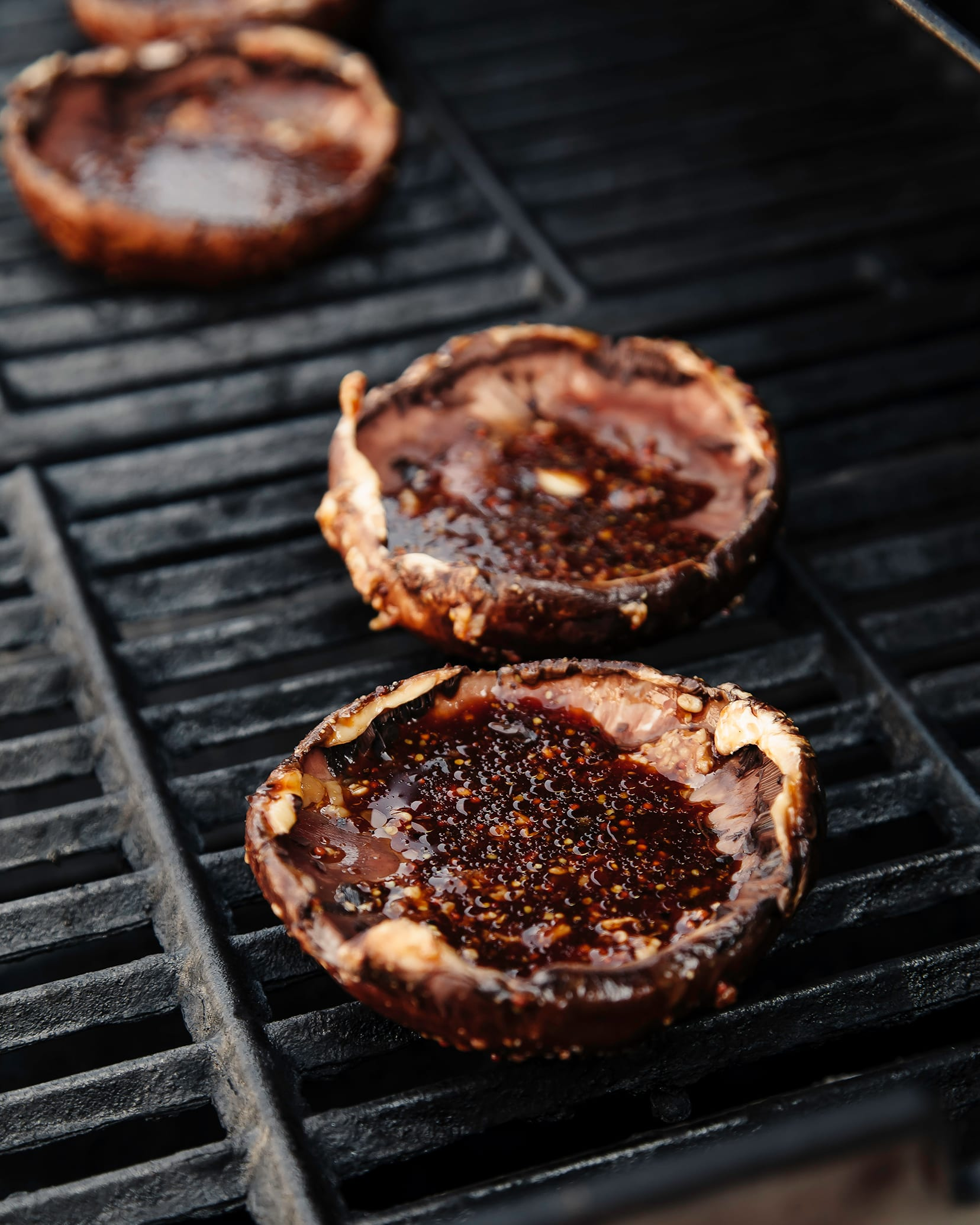 Image shows marinated portobello mushrooms on a grill outdoors.