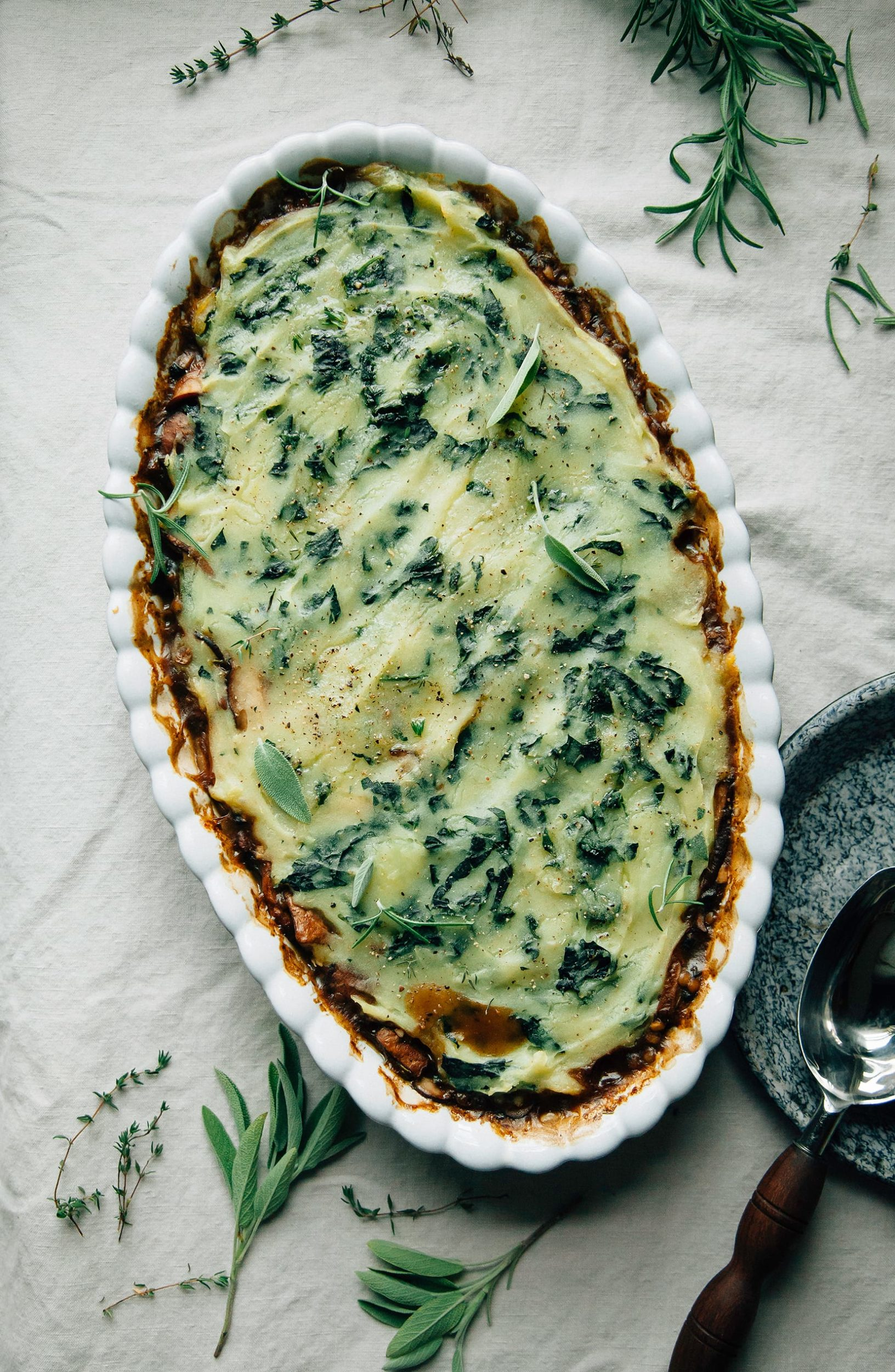 An overhead shot of a mushroom gravy pie topped with kale mashed potatoes in a baking dish.