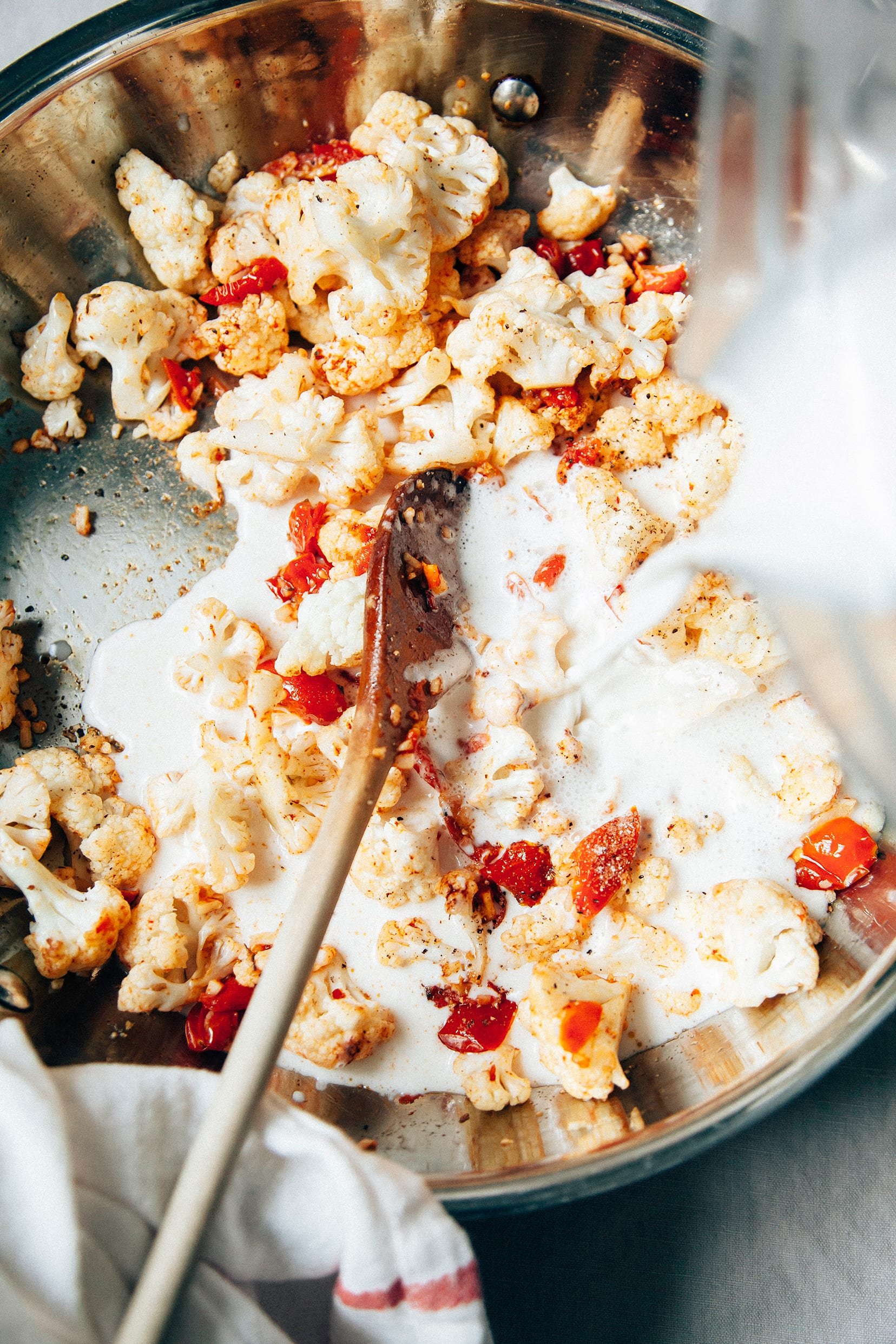 Image shows a creamy sauce being poured into a pan with tomatoes and cauliflower.