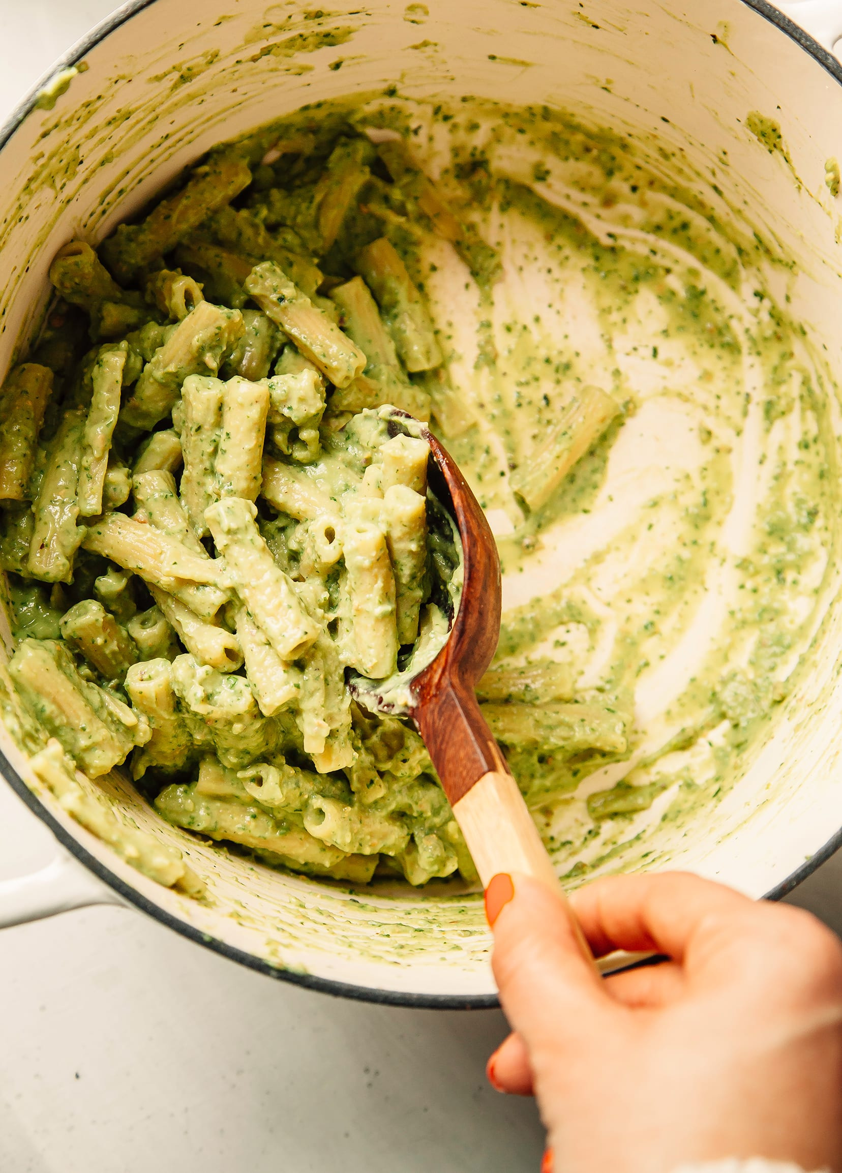 An overhead shot of avocado pesto pasta being stirred in a white pot.