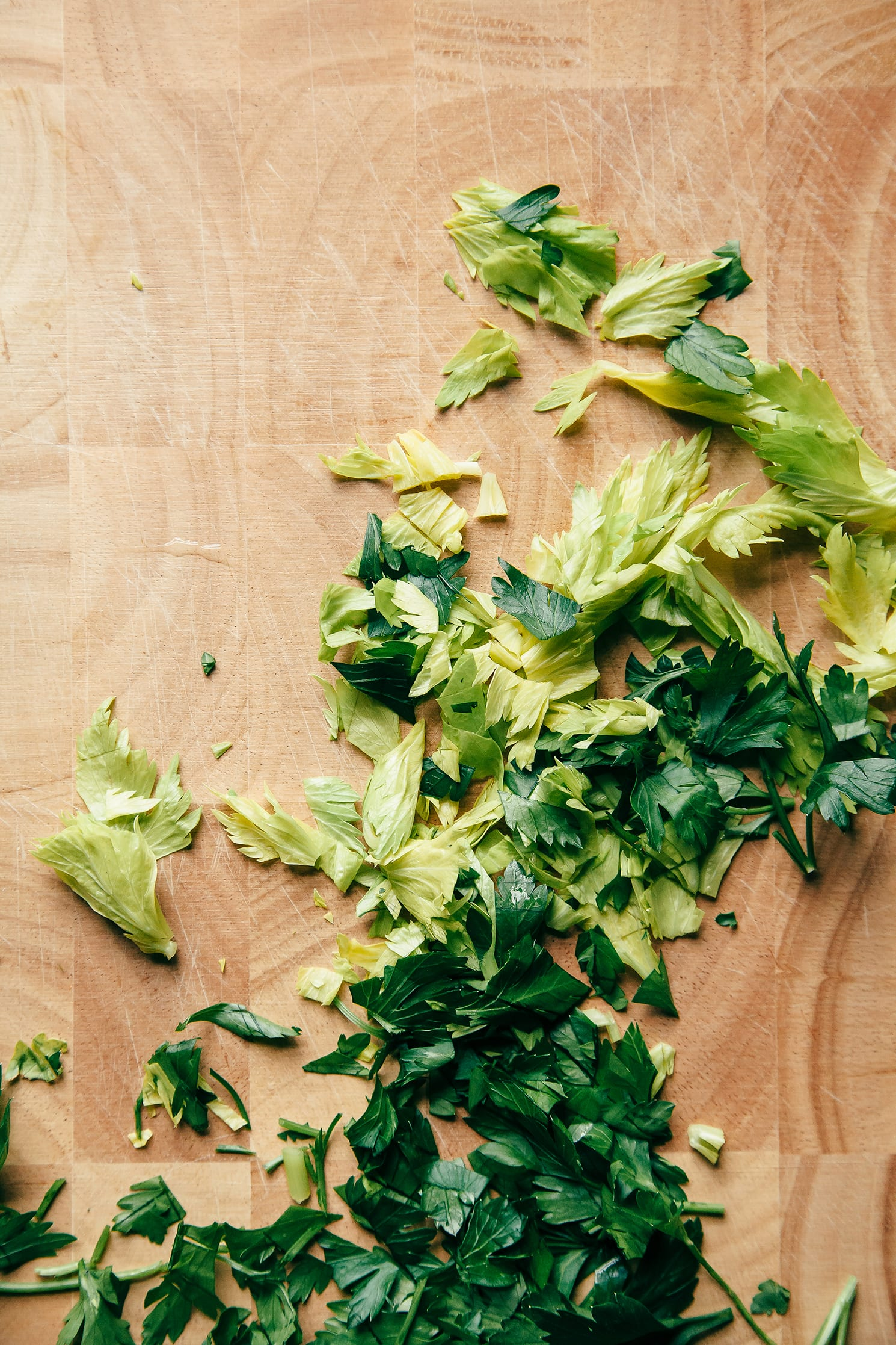 Image shows parsley and celery heart leaves on a cutting board.