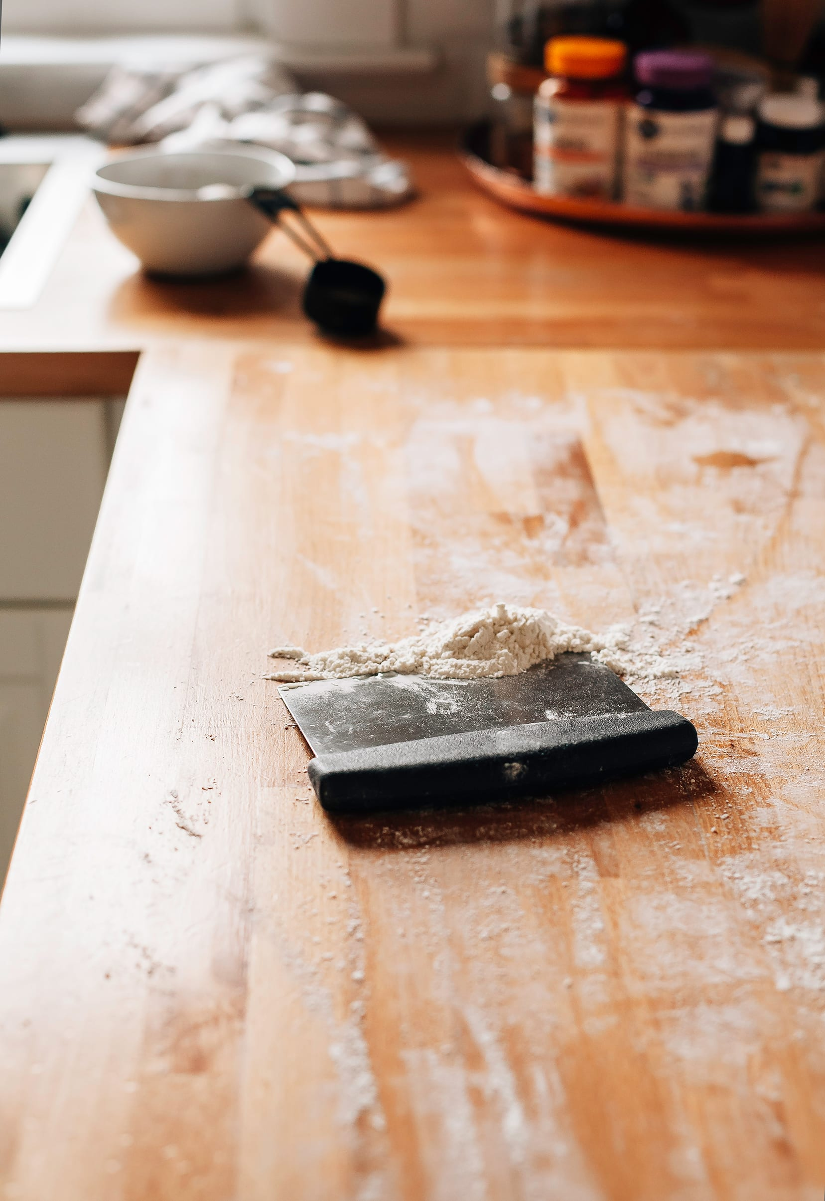 Image shows a bench scraper with gathered up dusting flour on top of a butcher block countertop.