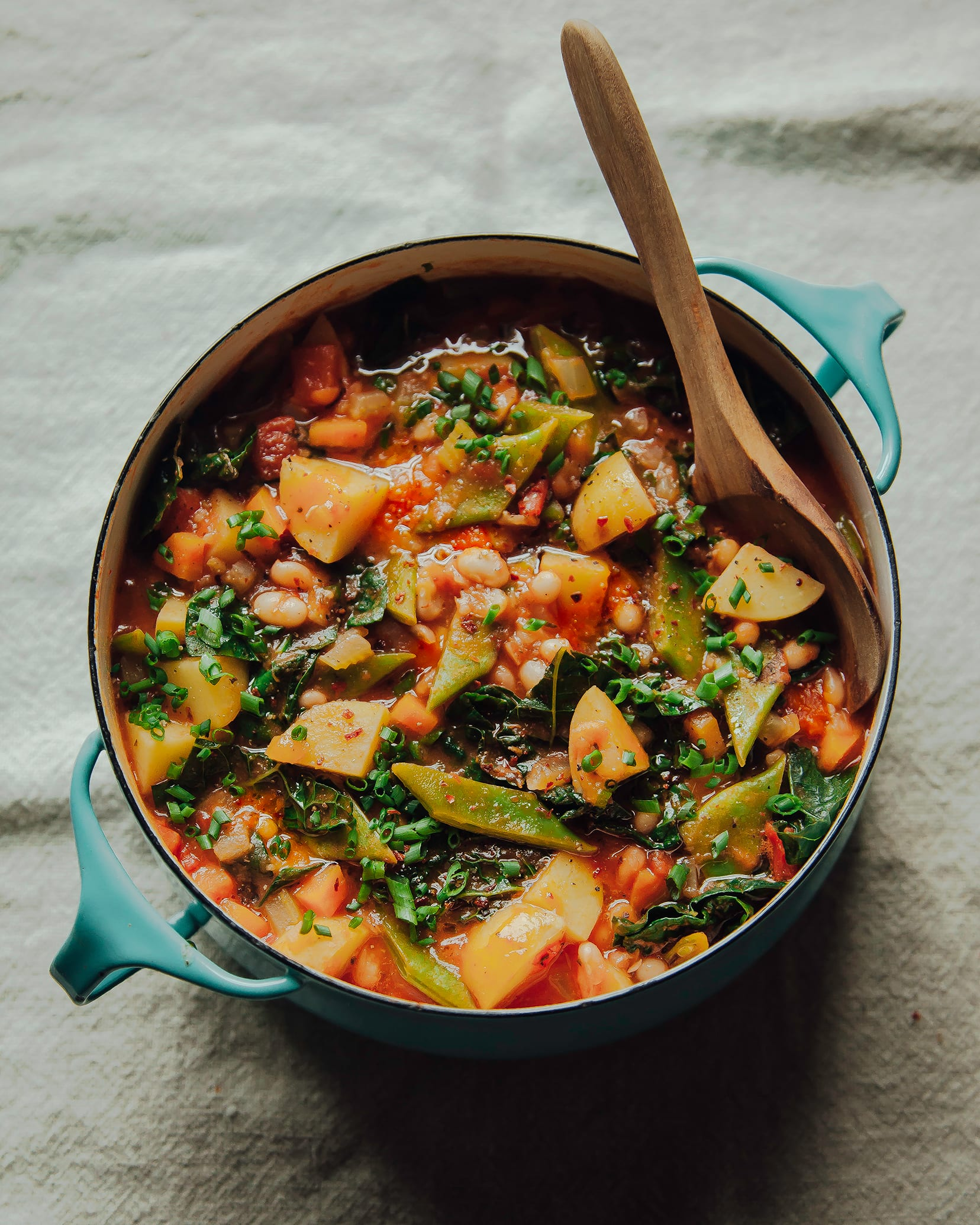 An overhead shot of a tomato-y white bean and potato stew in a turquoise pot.