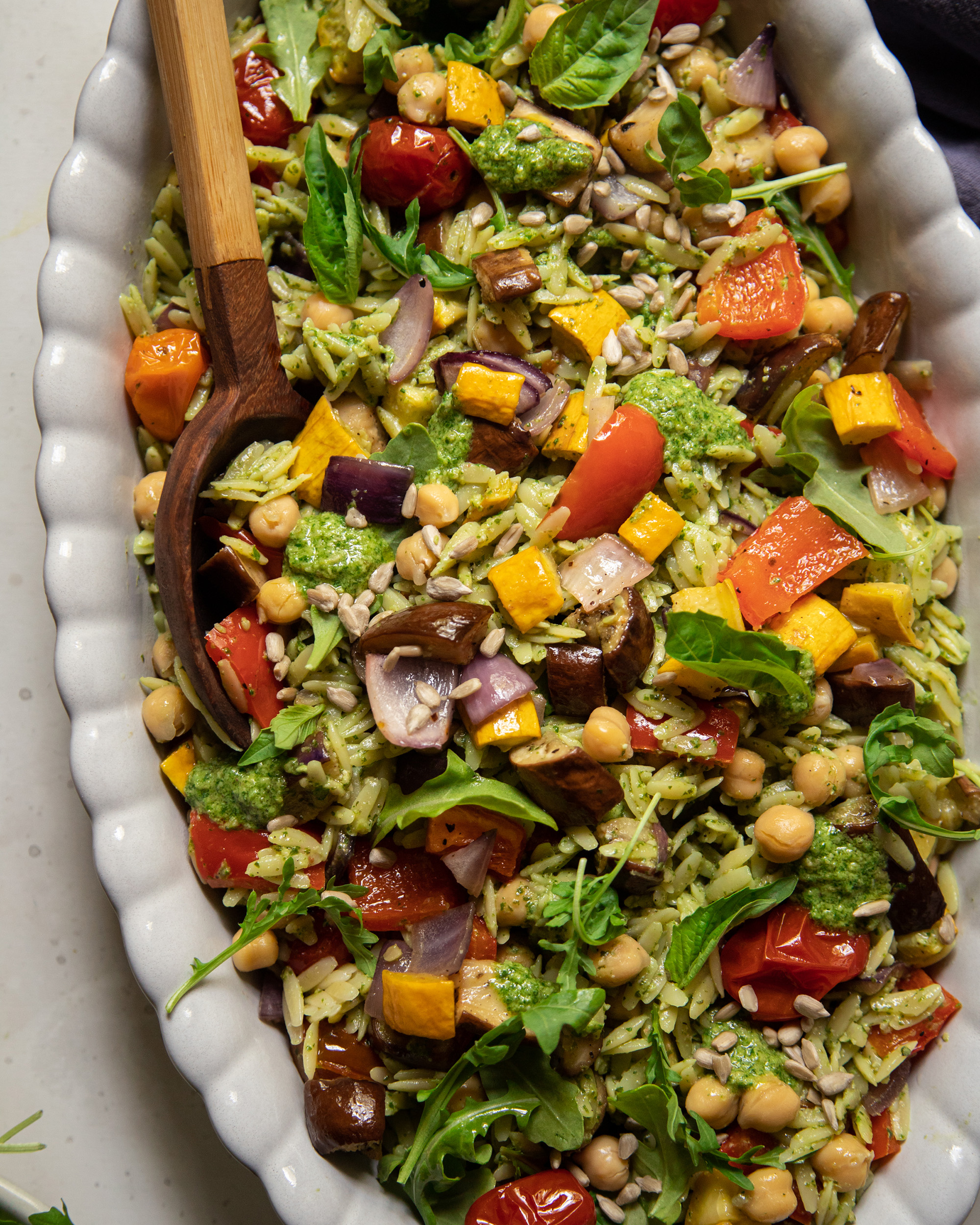 An up close, overhead shot of a pesto orzo salad with dices of roasted vegetables and chickpeas. The dressing is creamy and bright green. There is a wooden spoon sticking out of the dish of salad.