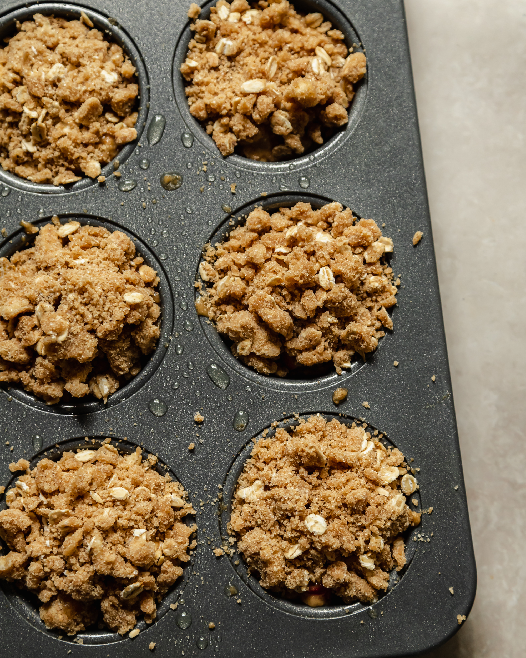 Image shows muffins topped with a crumble topping pre-baking.