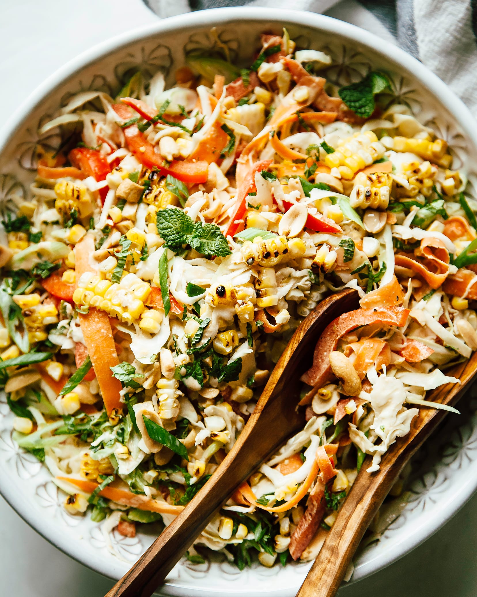An up close, overhead shot of charred corn slaw with peanut butter lime dressing. The slaw is served in a white patterned bowl with wood serving tongs.