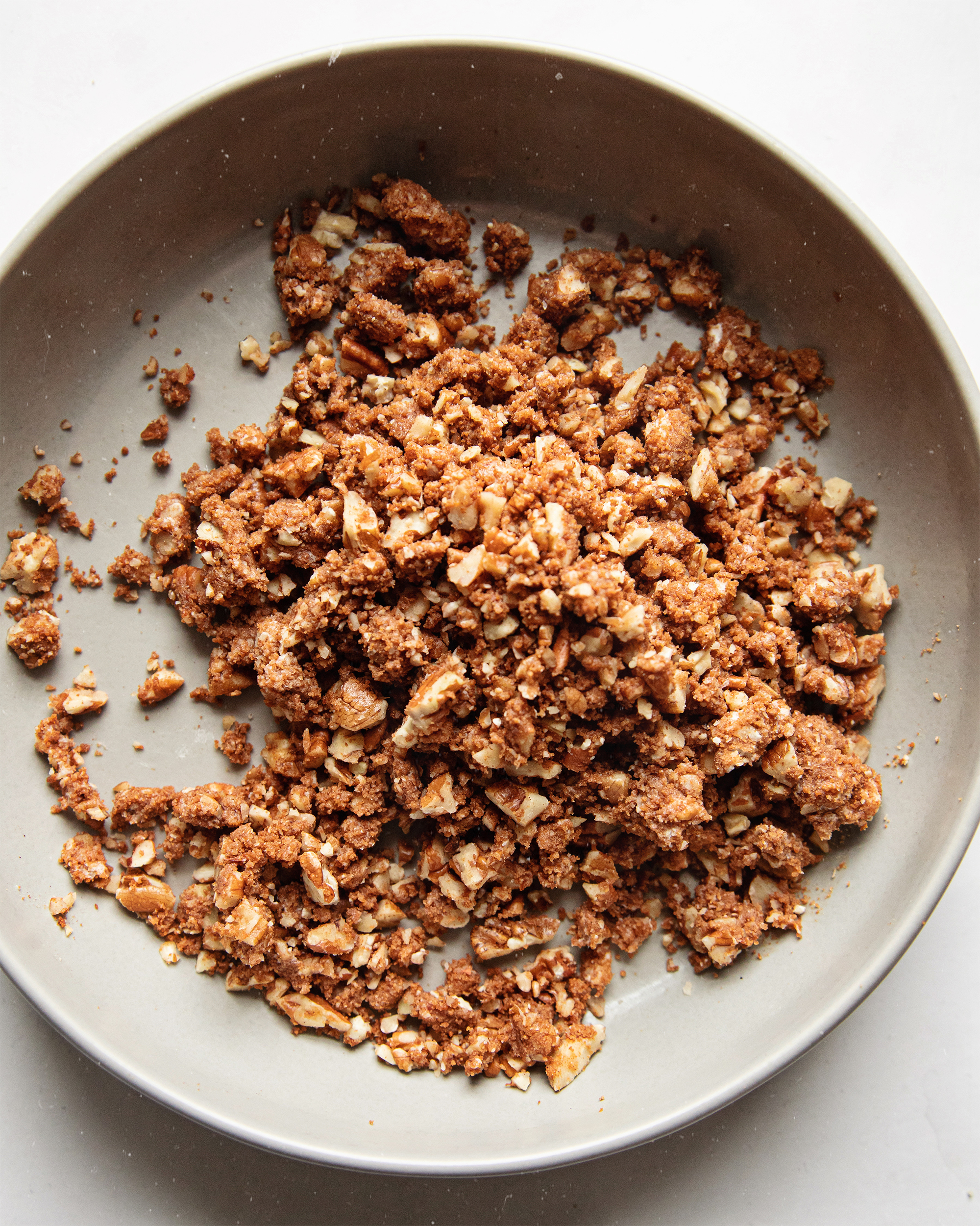 AN overhead shot of finished pecan streusel in a grey bowl on a white background.