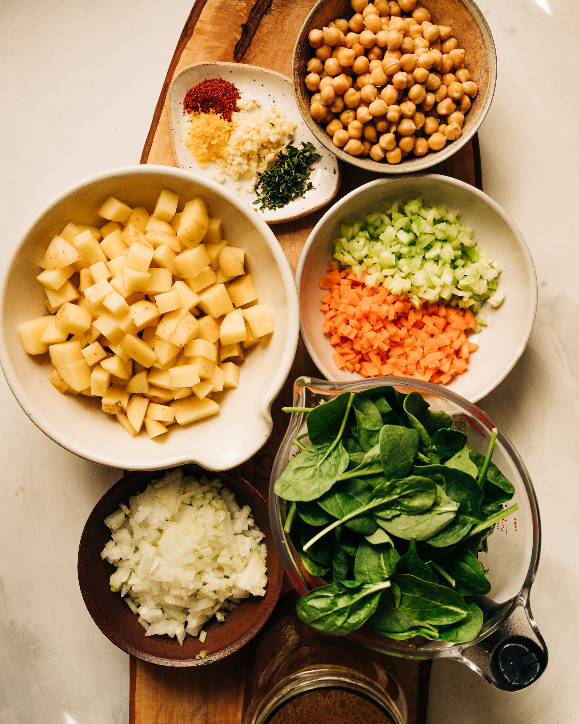 An overhead shot of prepped and chopped ingredients including celery, carrots, onions, baby spinach, minced garlic, thyme, and more,