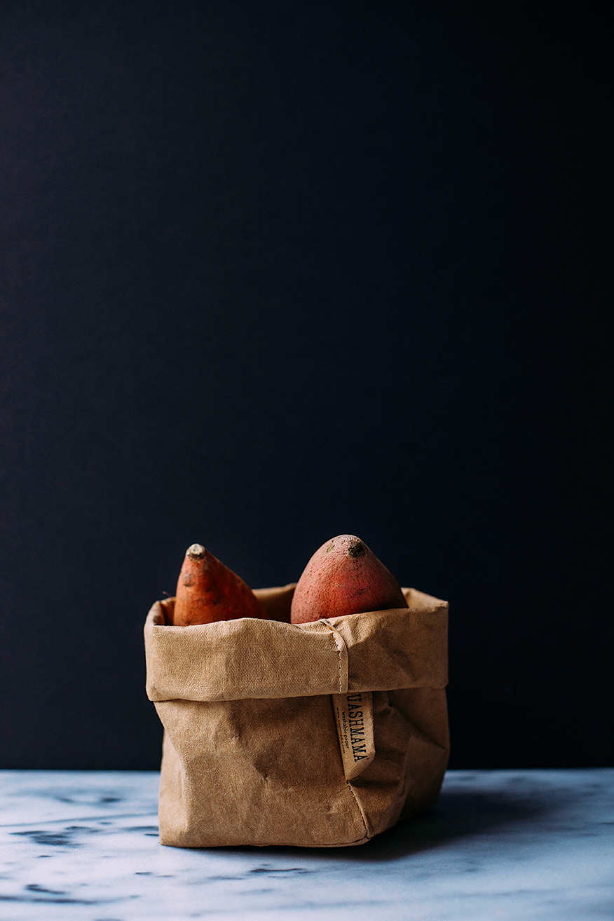 A head on shot of a brown bag with sweet potatoes in it.