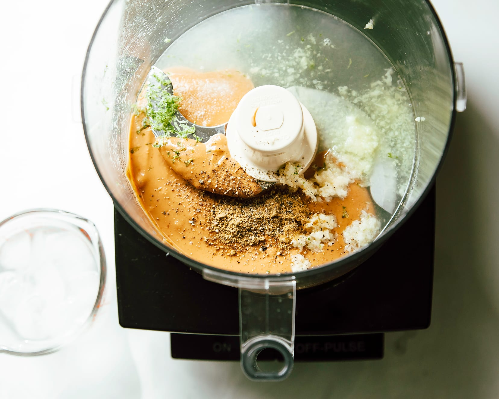 An overhead shot of a food processor with peanut butter lime dressing ingredients inside, pre-mixing.