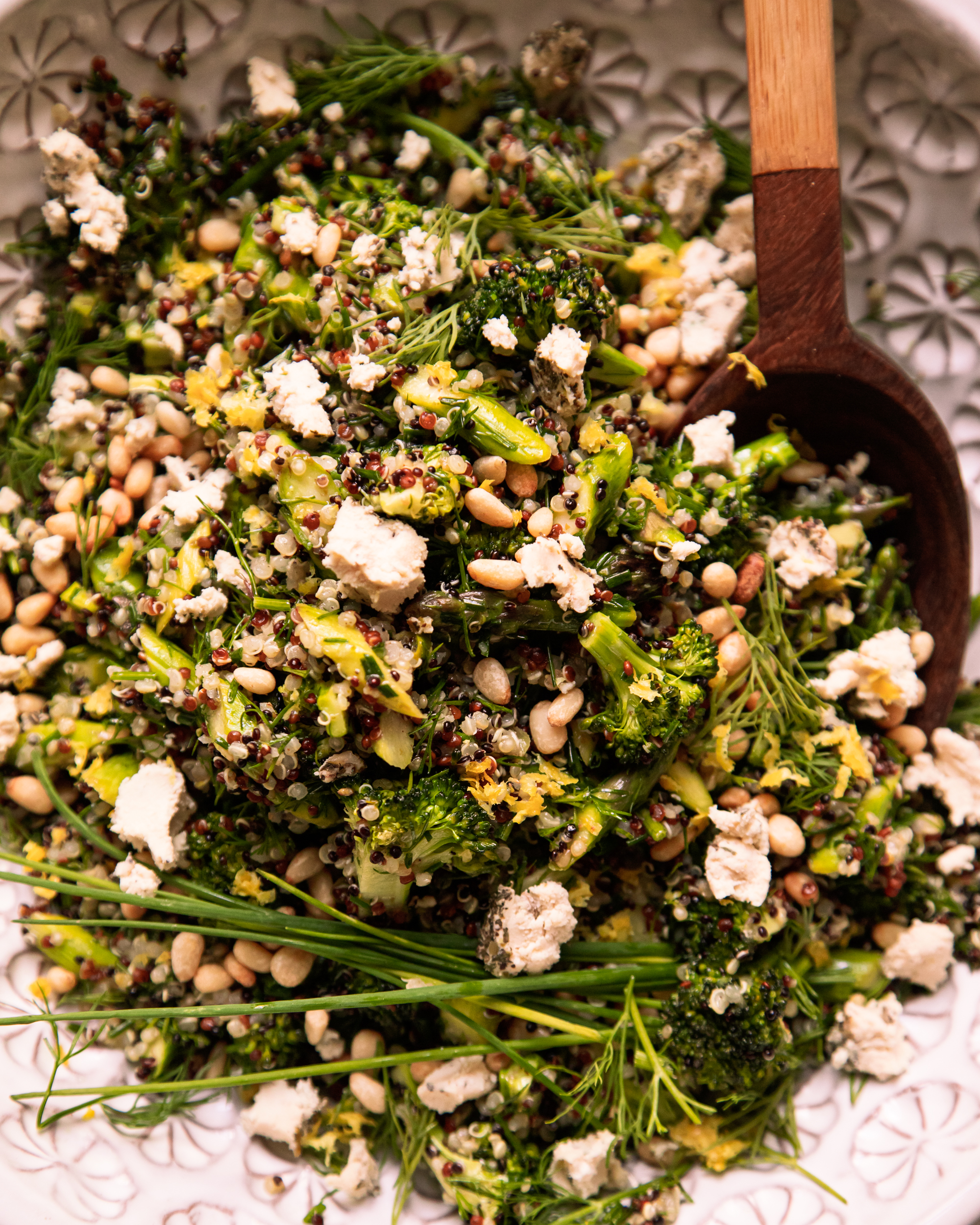 Image shows a green love quinoa salad in a patterned white bowl. The salad is garnished with whole blades of chives and bits of soft vegan cheese.