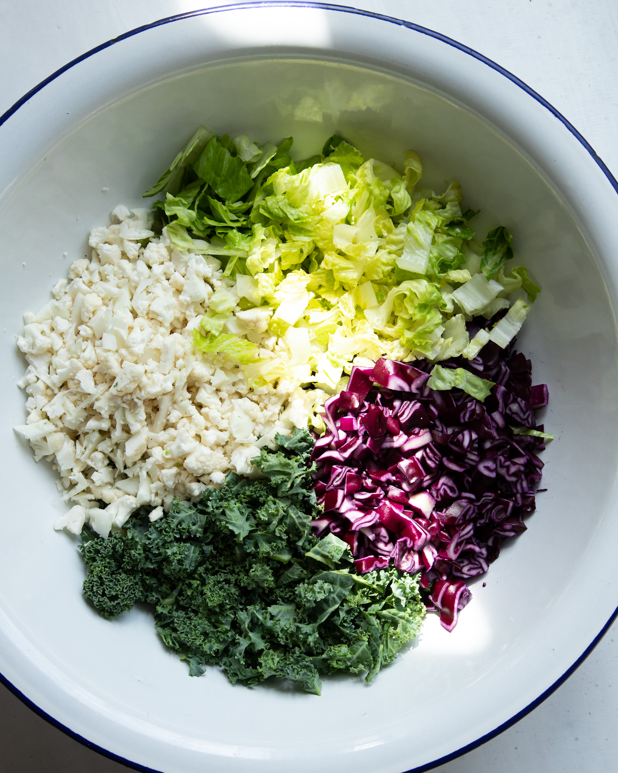 Image shows chopped vegetables in a large white bowl, before mixing into a salad with dressing.