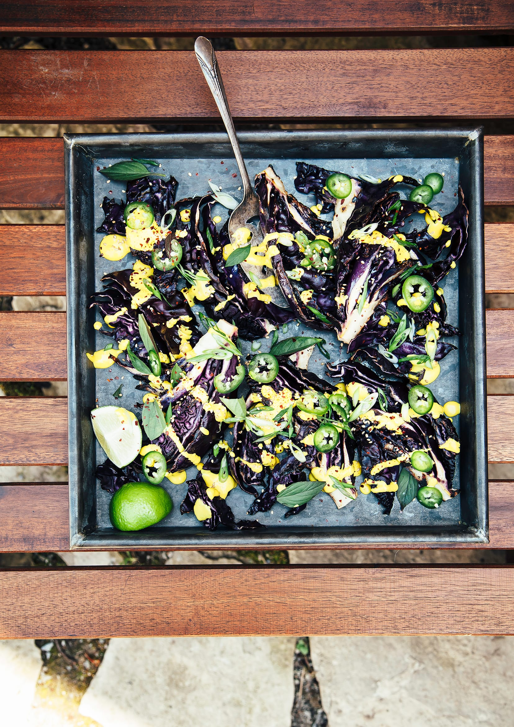 Image shows a dark metal tray with grilled cabbage wedges, drizzled in a creamy bright yellow sauce and topped with chopped herbs and sliced jalapeños .