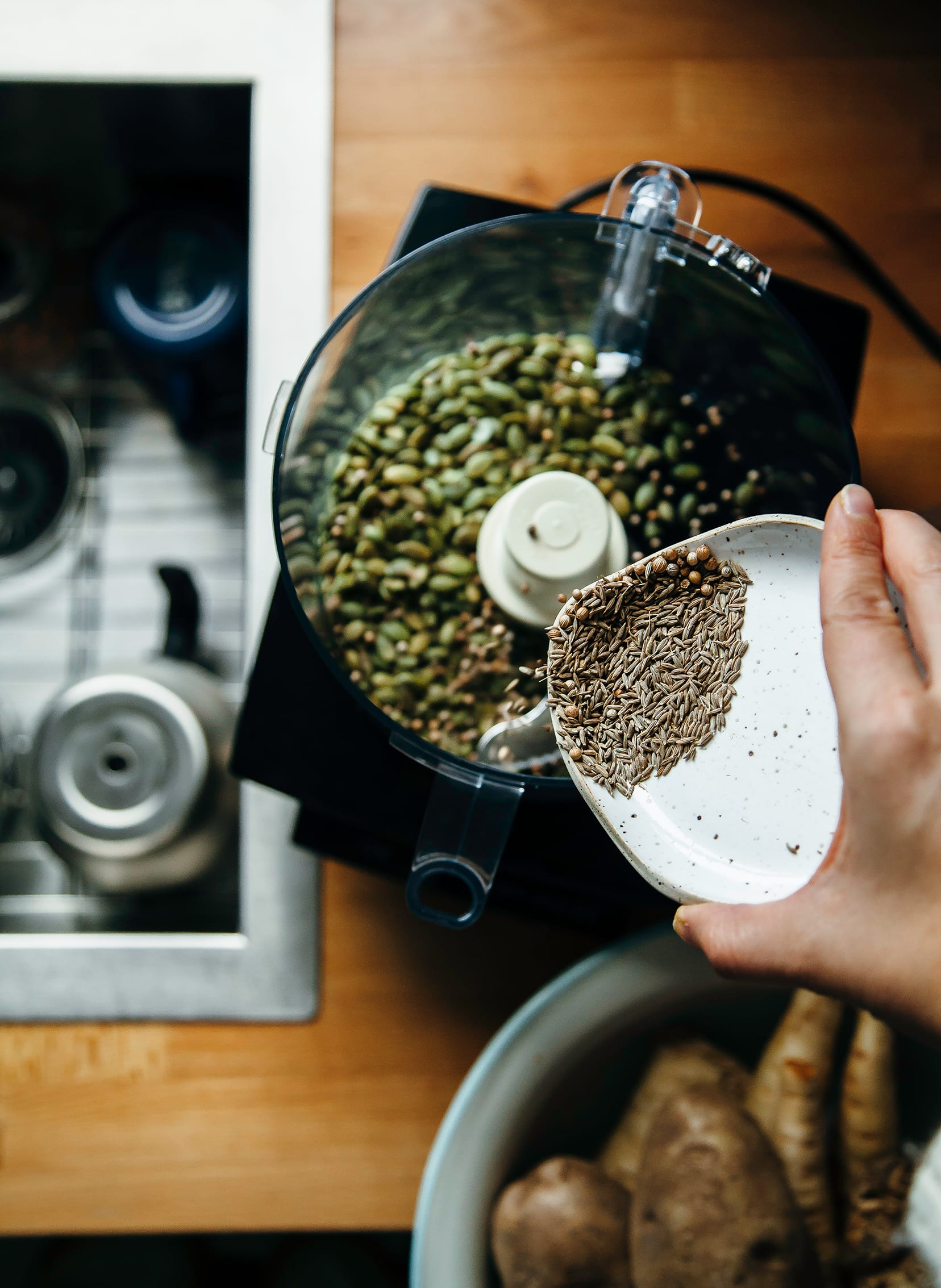 Image shows a hand pouring whole spices into a food processor.