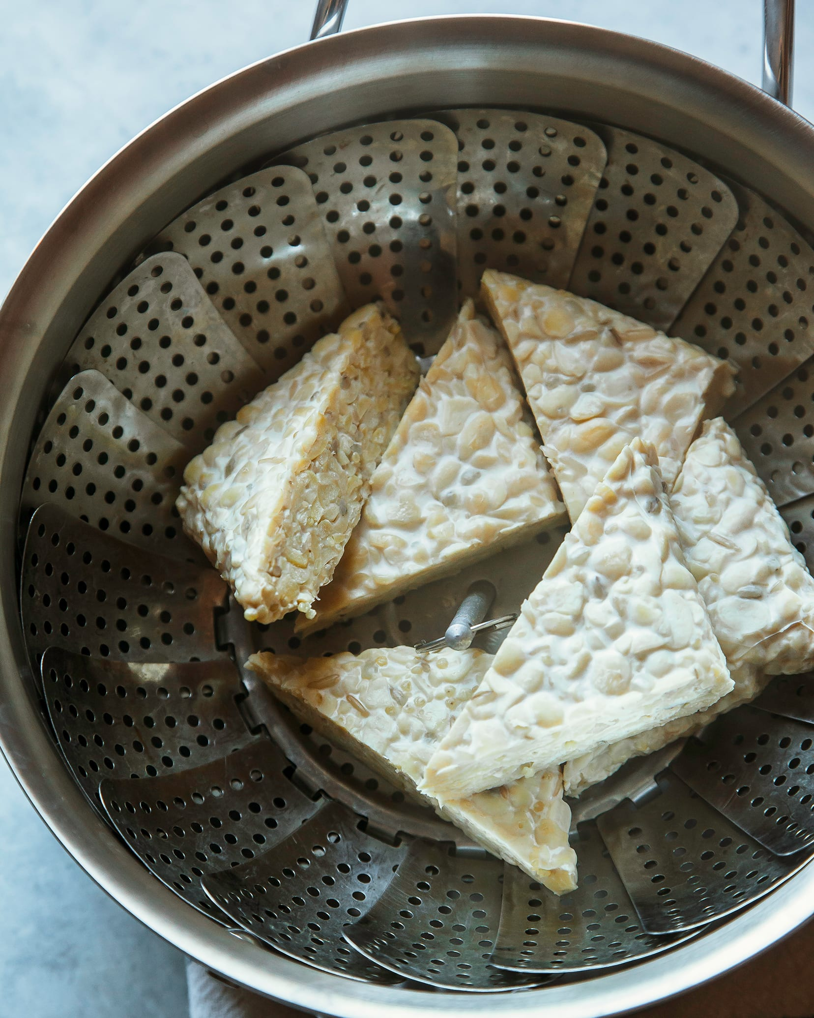 Image shows triangular pieces of tempeh in a steamer basket.