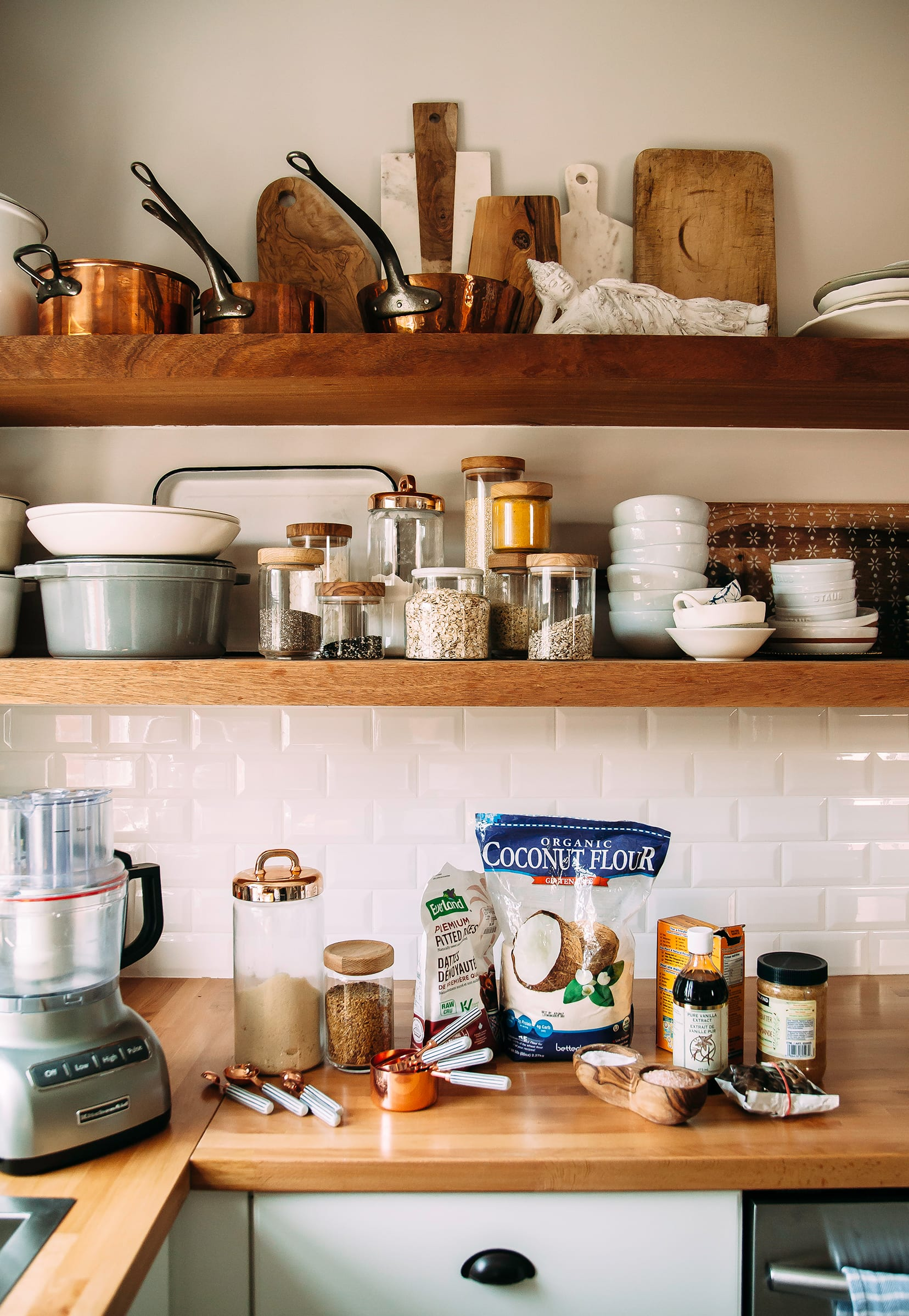 A photo of the open shelves in my kitchen with the cookie ingredients and a grey food processor on the butcher block counter.