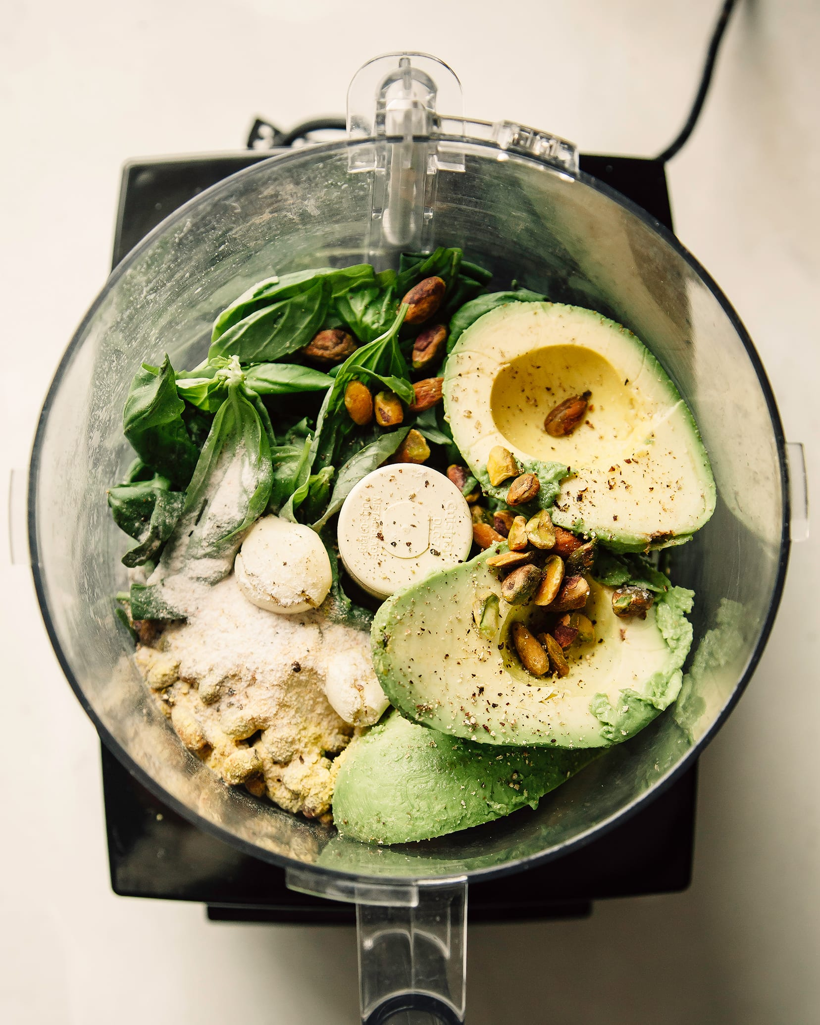 An overhead shot of an open food processor with avocado pesto sauce ingredients.