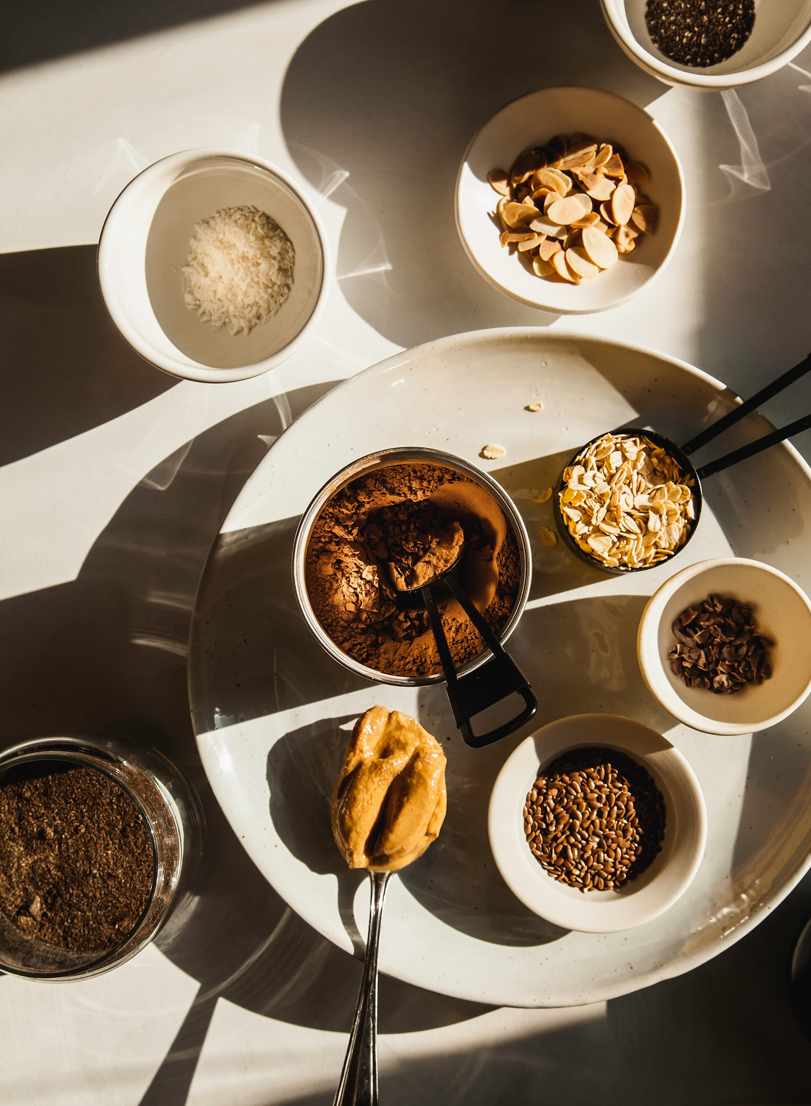 An overhead shot of hearty chocolate oat smoothie ingredients in direct sunlight.