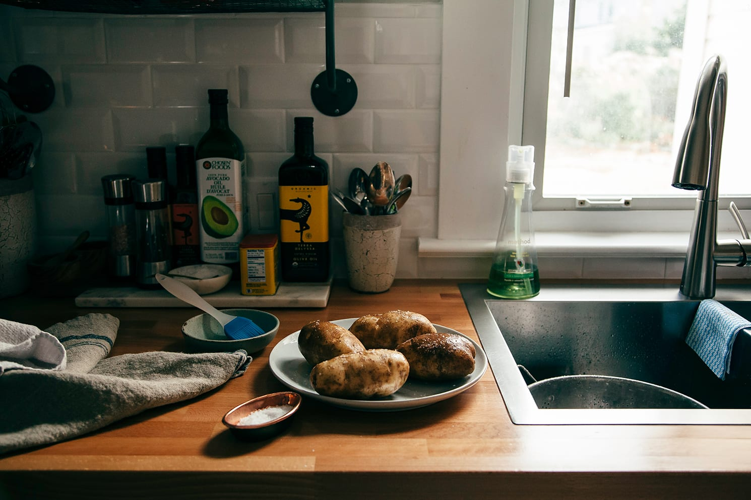 Image shows baking potatoes on a plate on top of a kitchen counter. They are topped with coarse salt.