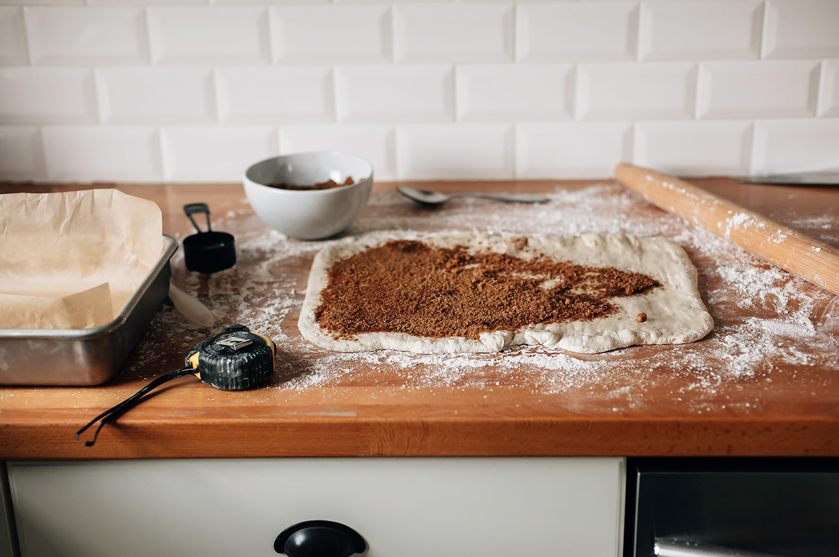 Image shows some rolled out dough with a brown sugar mixture spread on top of the surface of the dough.