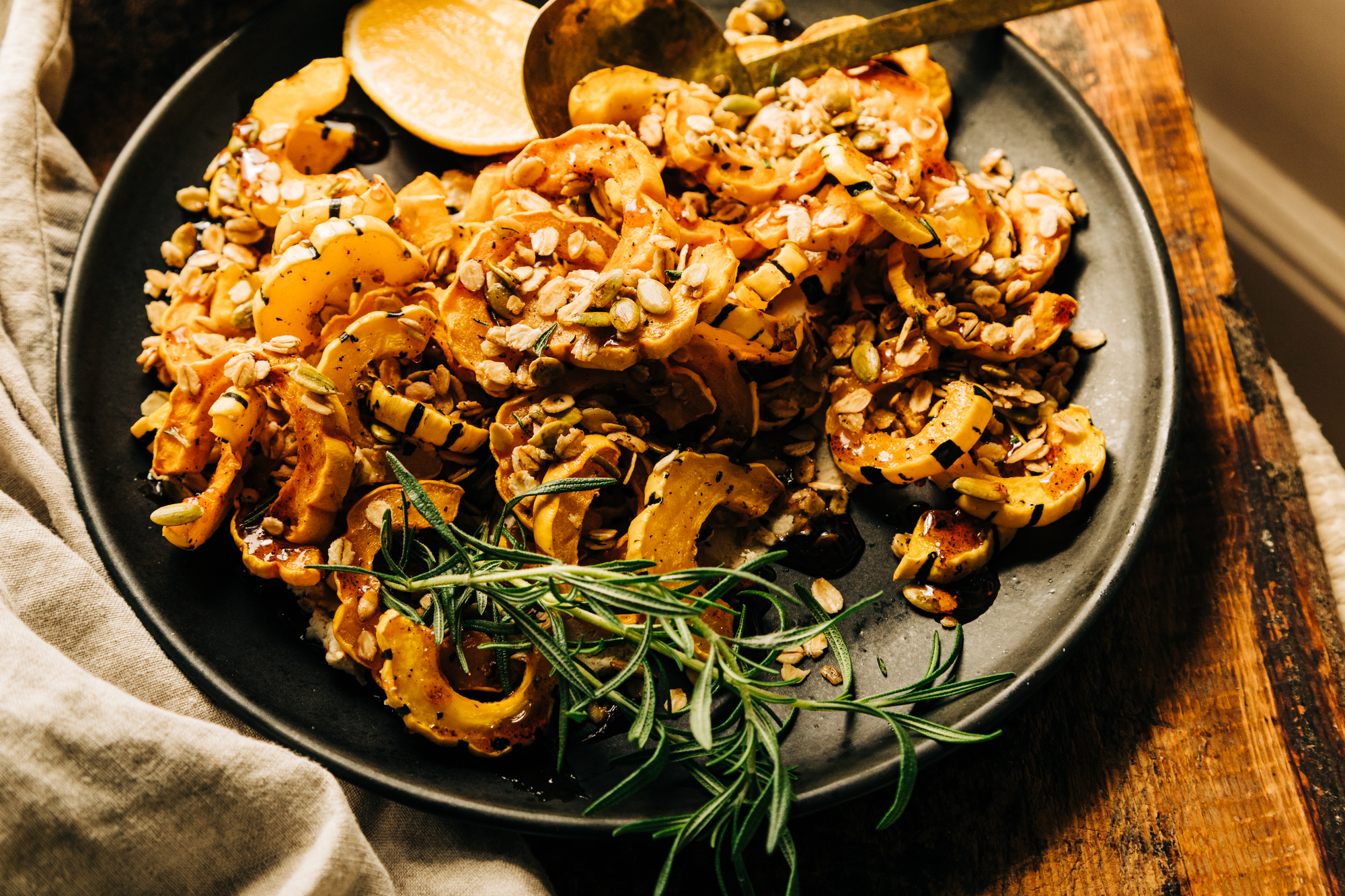 A 3/4 angle shot of a delicata squash side dish topped with savoury rosemary granola and spiced maple syrup.