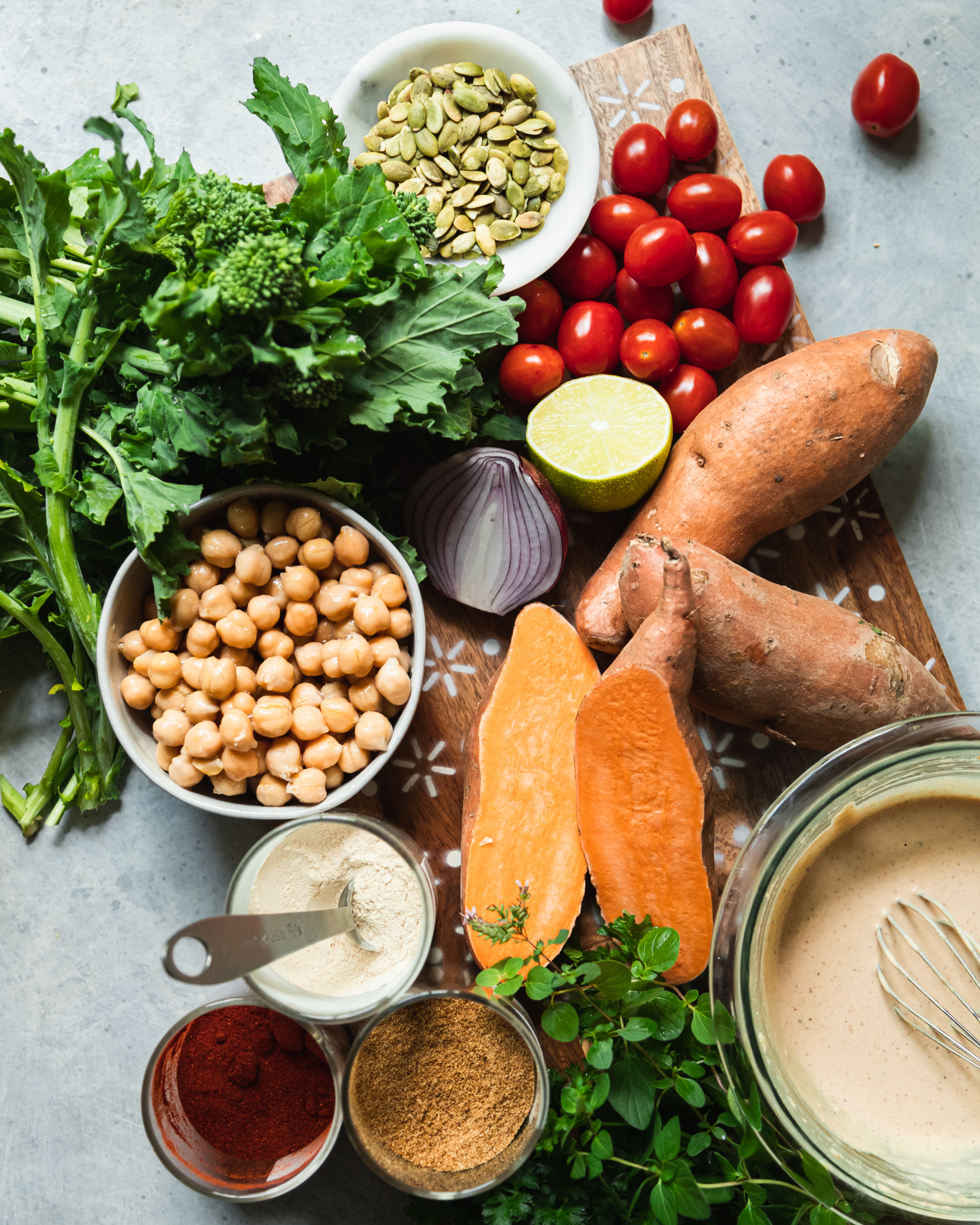 An overhead shot of ingredients for a healthy sheet pan dinner with sweet potatoes and broccoli rabe.