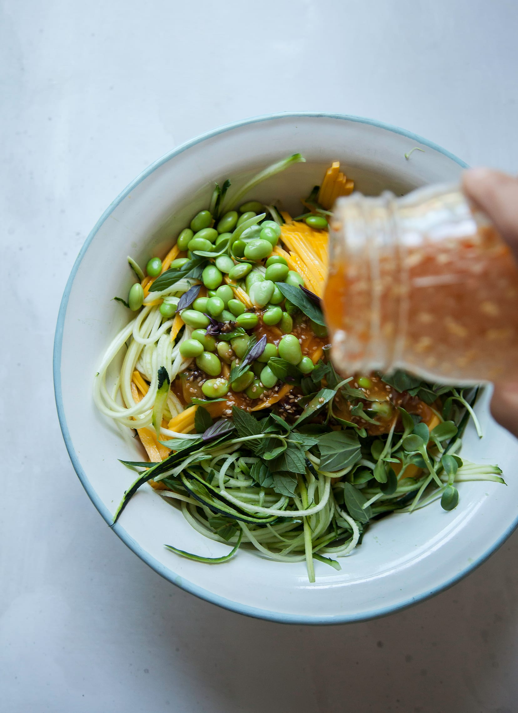 Image shows a hand pouting a light orange dressing over a green vegetable noodle salad with edamame.