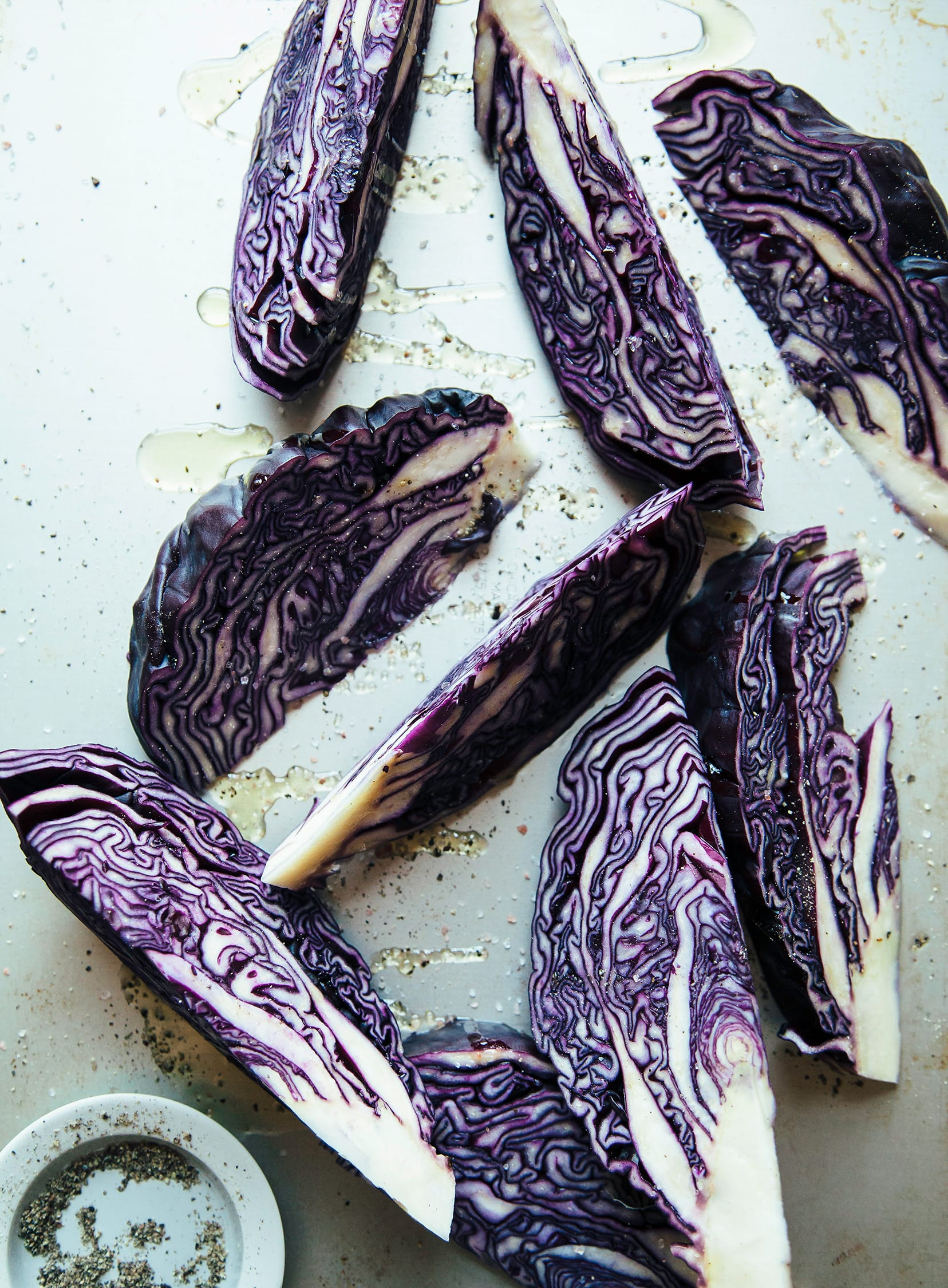 Overhead shot of purple cabbage wedges coated in oil and sprinkled with salt and pepper.