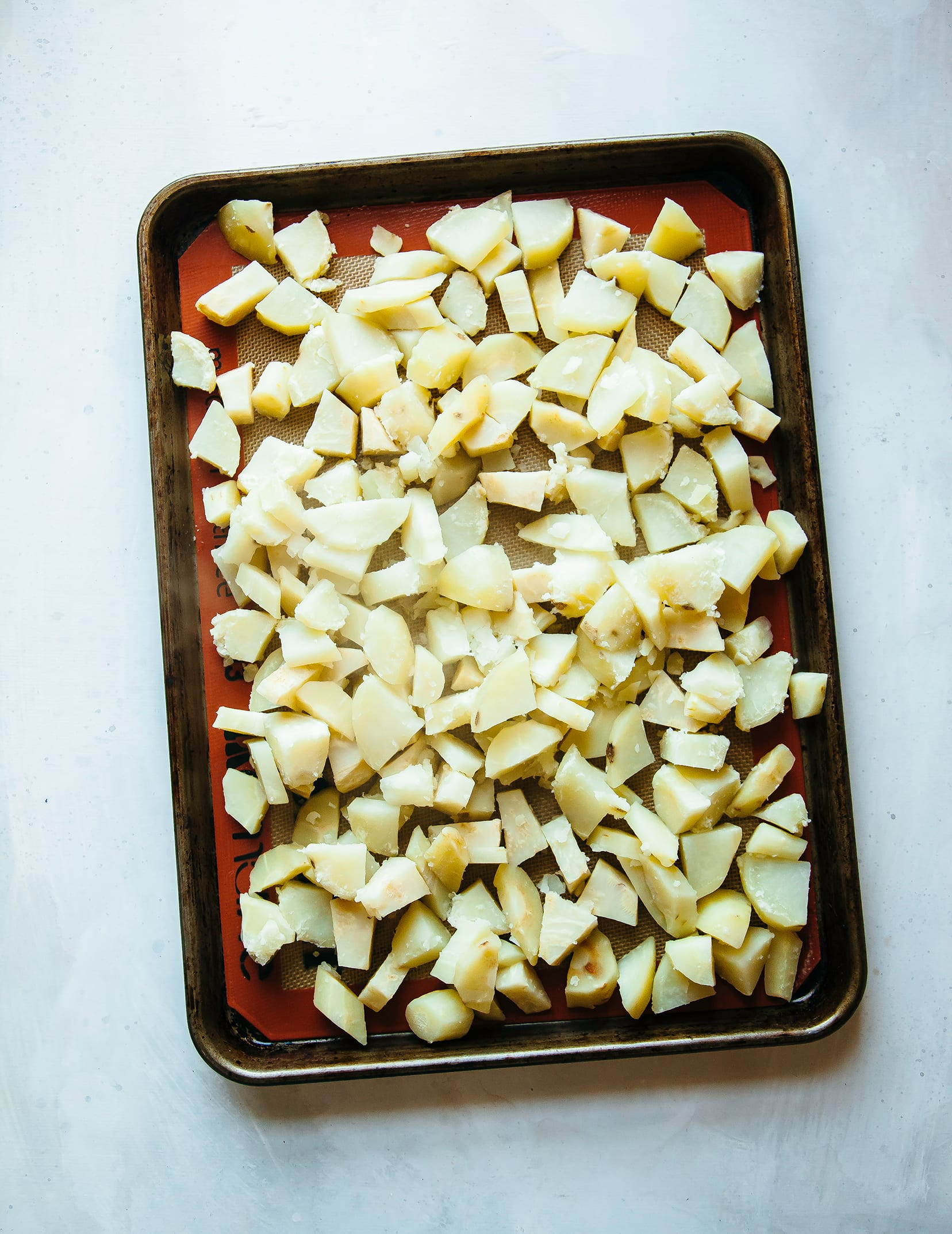 Image shows cooked cubes of root vegetables on a baking sheet.