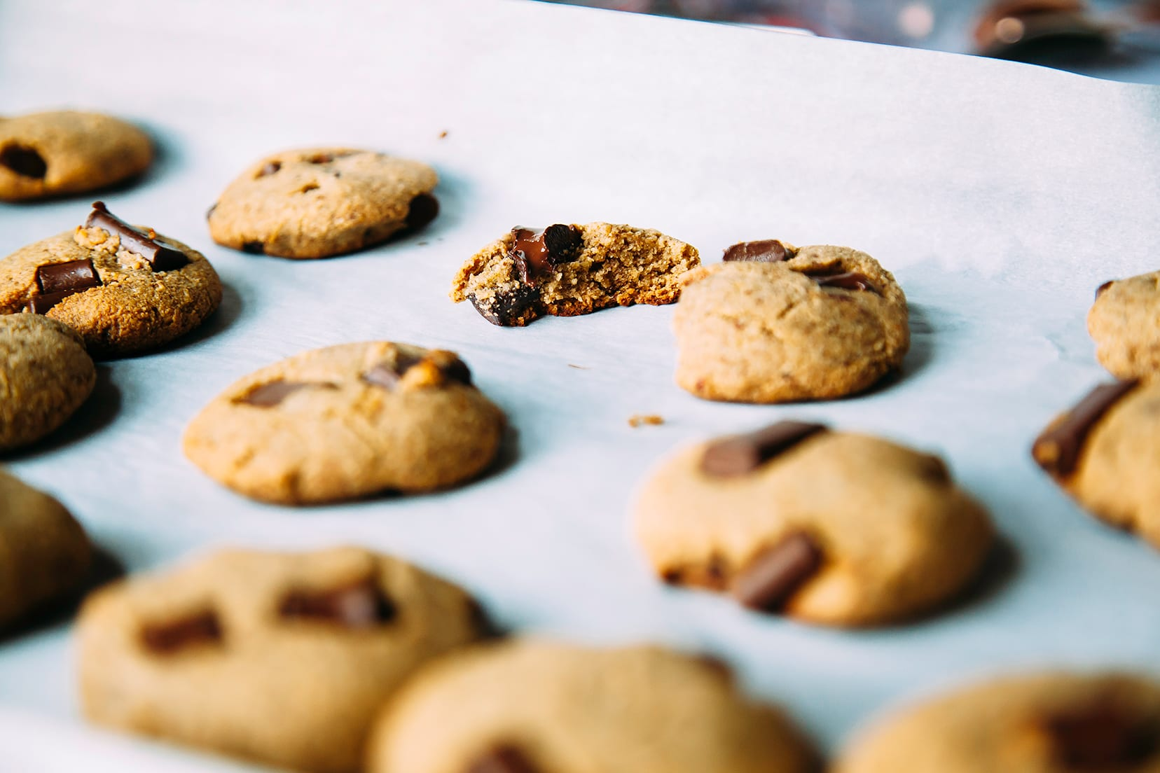 A side angle of chocolate chunk wonder cookies. One of the cookies is split in half to reveal the moist interior.