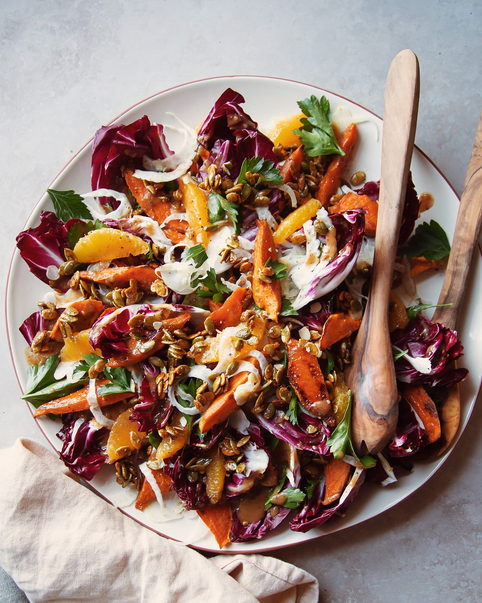 An overhead shot of a roasted sweet potato and radicchio salad with coriander candied pumpkin seeds, shaved fennel and orange.