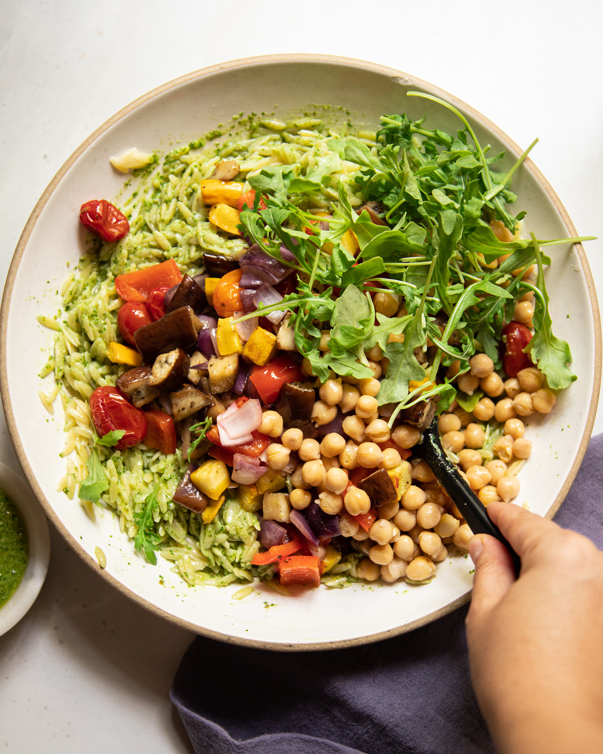 An overhead image shows a hand stirring together an orzo salad with vegetables and chickpeas.