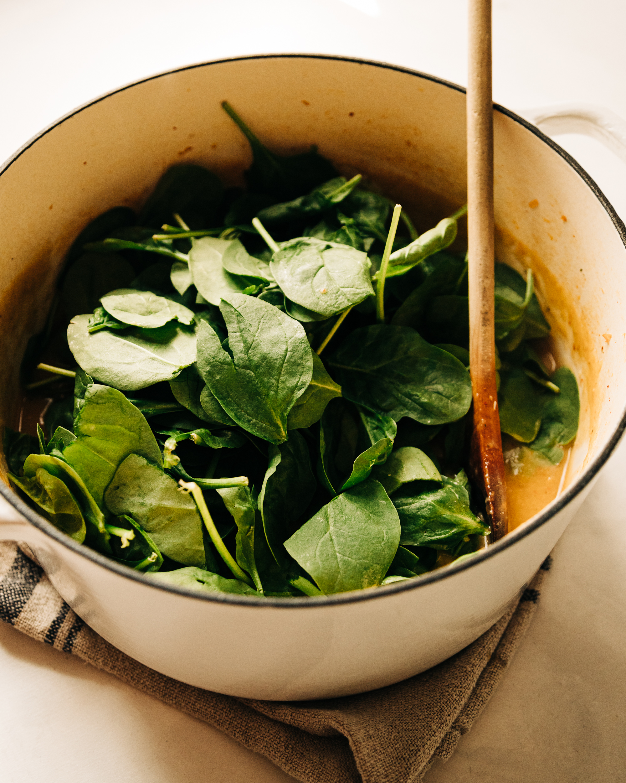 A 3/4 angle shot of a pile of baby spinach in a dutch oven style pot, on top of a soup.